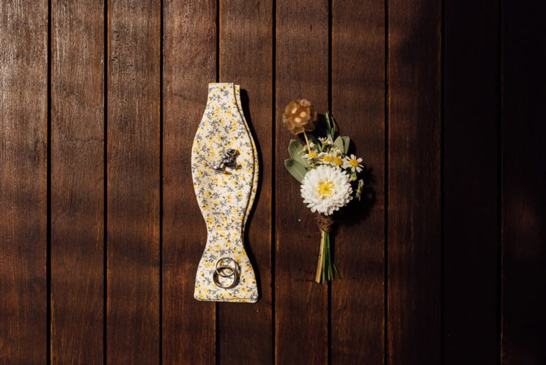 daisy boutonniere and yellow floral bow tie
