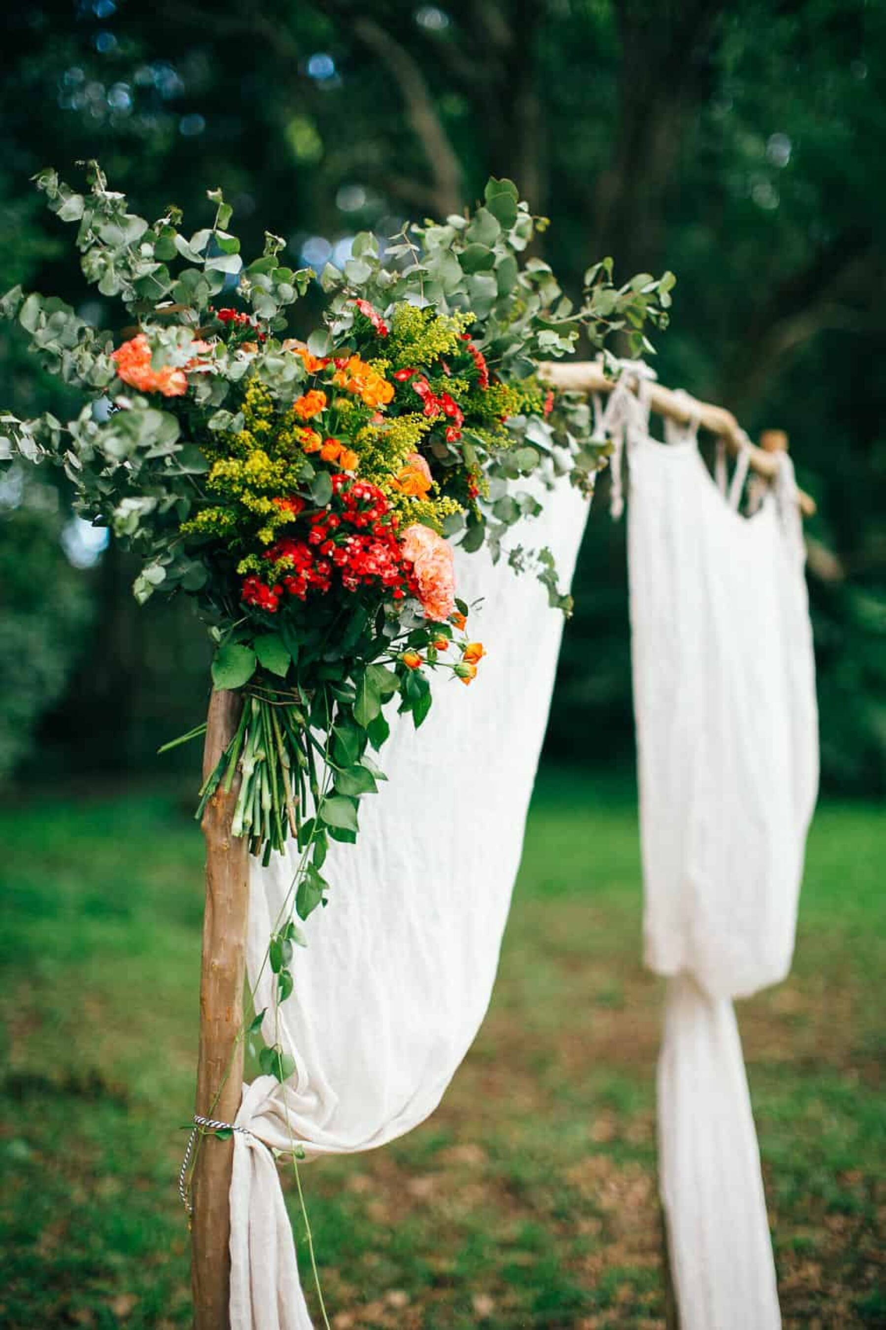 draped curtain wedding arbour with floral cluster