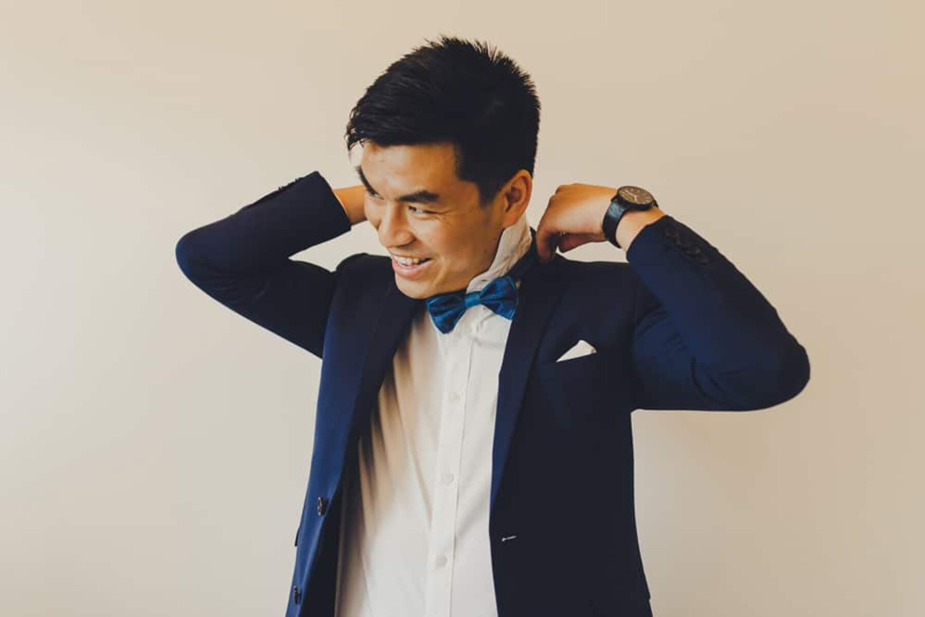 groom wearing royal blue suit and bow tie