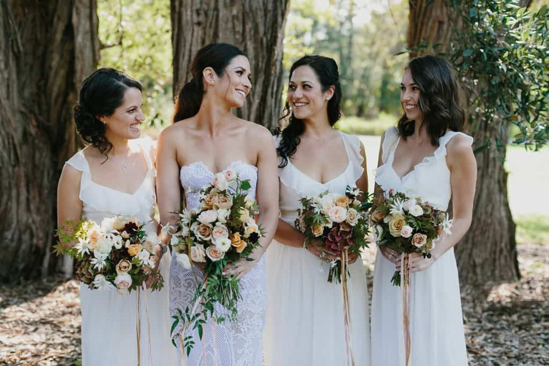 bridesmaids in white with peach-toned bouquets