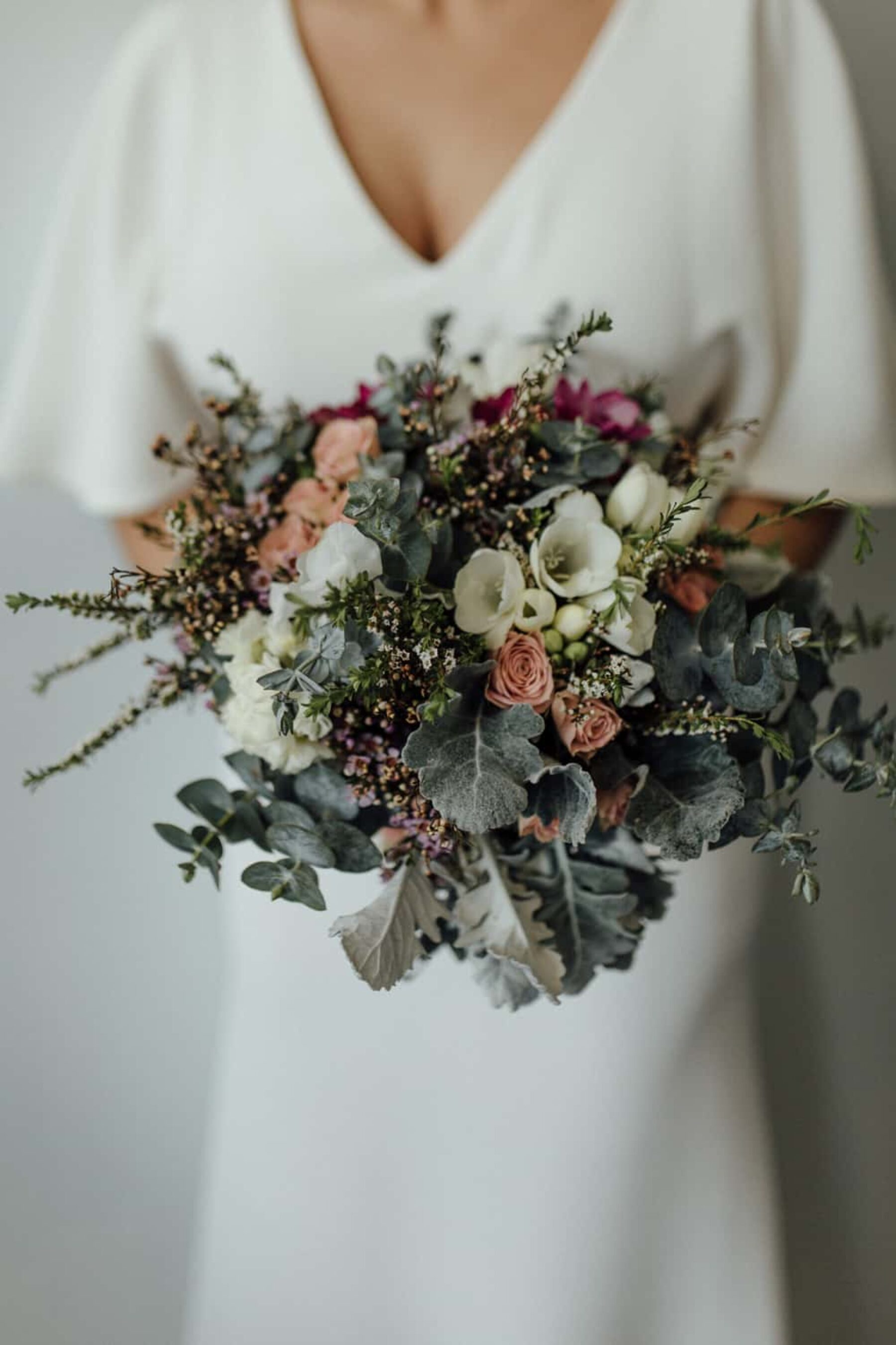 modern bride with rose and wax flower bouquet in muted tones