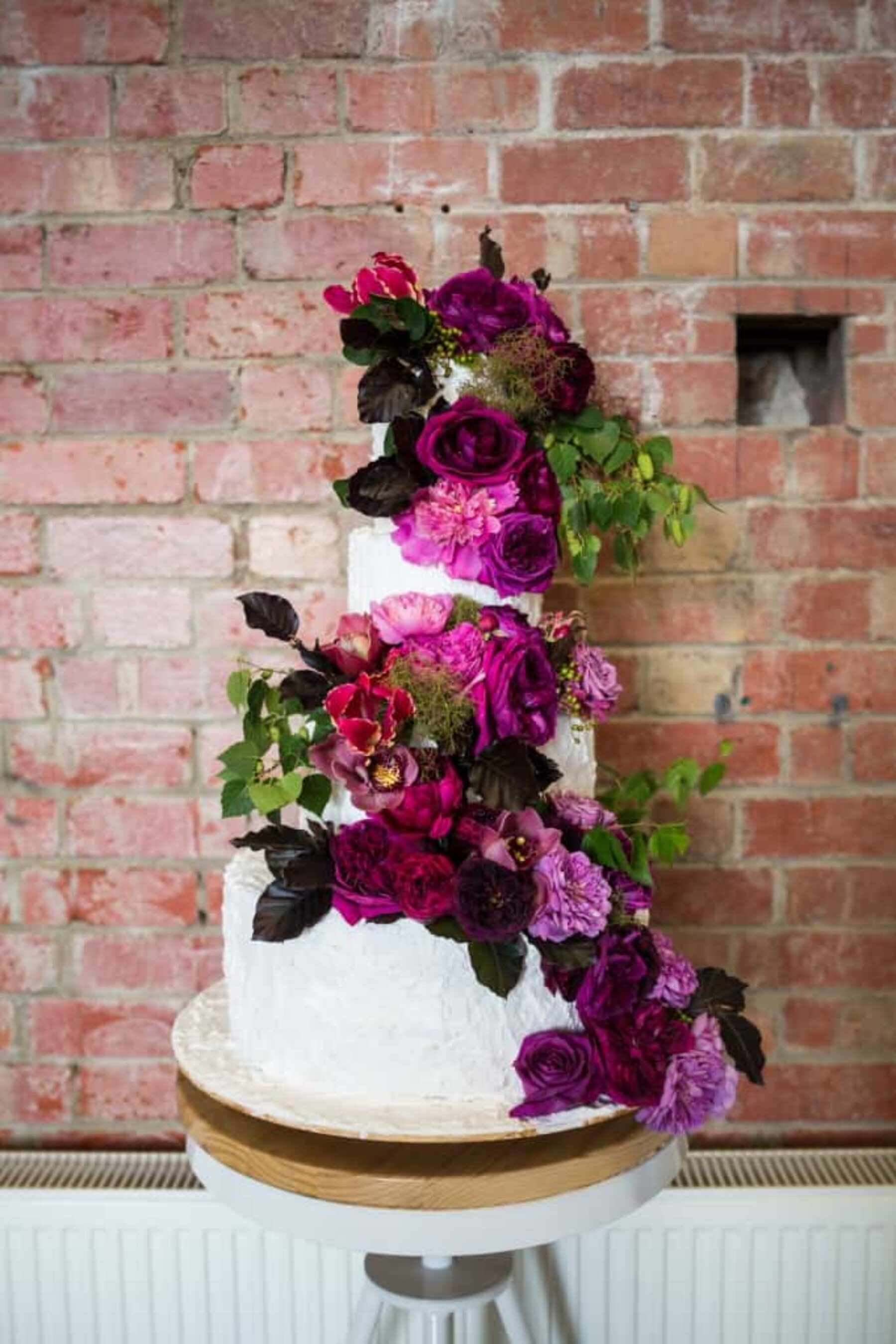 3 tiered wedding cake with fresh magenta and plum flowers