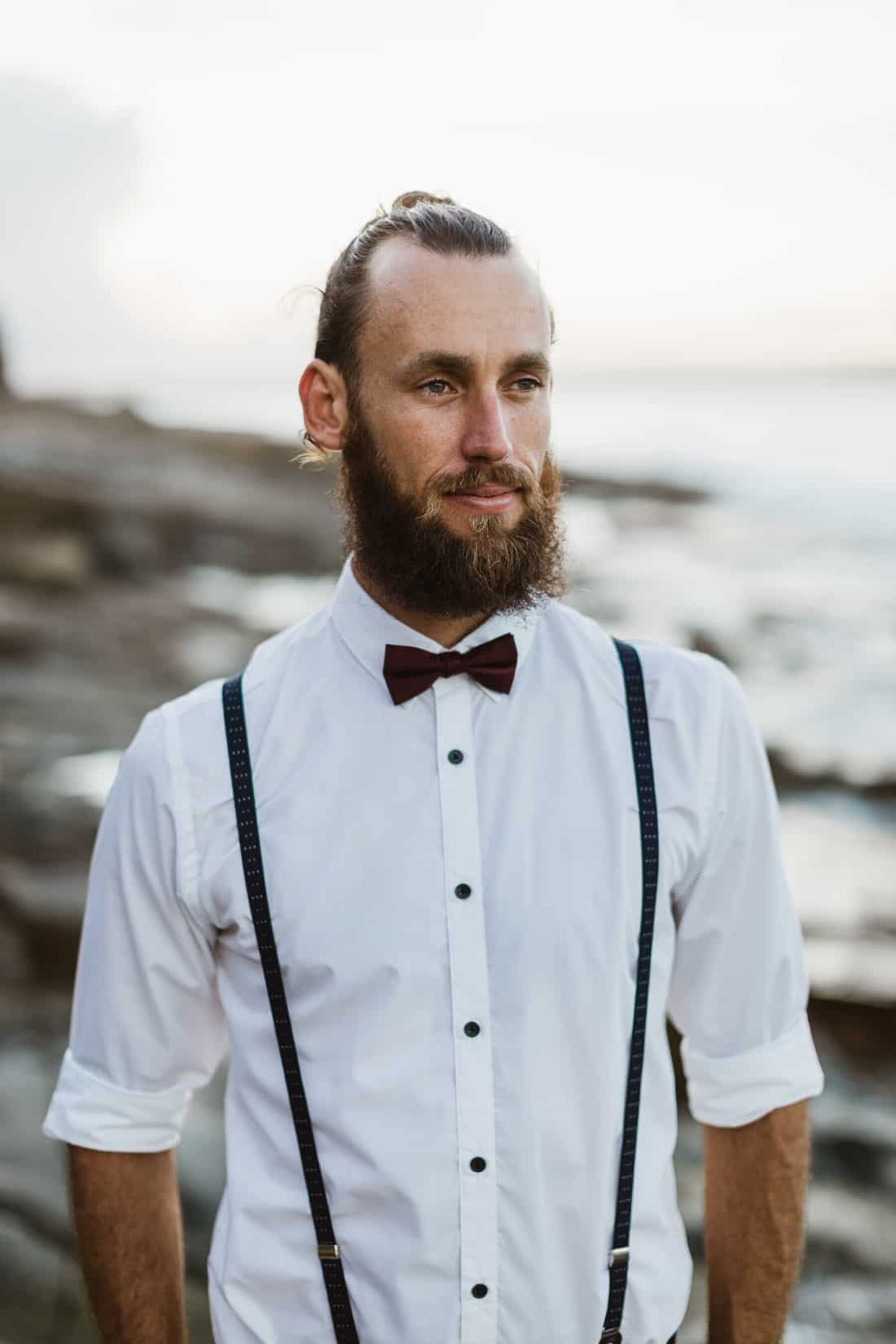 surfer groom with braces and bow tie