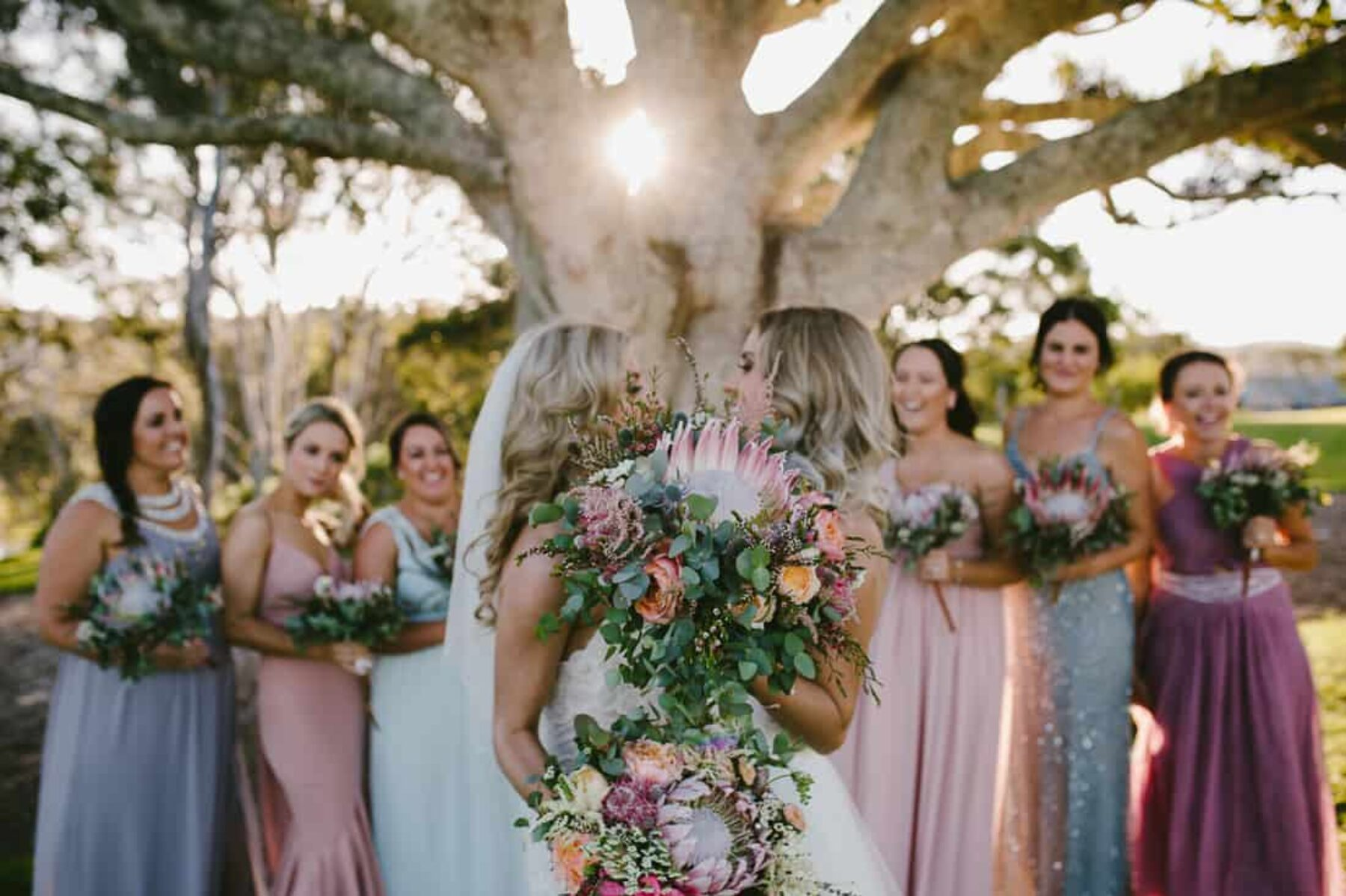brides and bridesmaids with protea bouquets