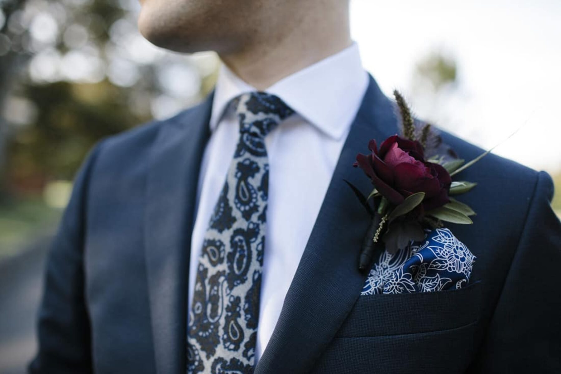 Stylish groom with paisley tie and pocket square