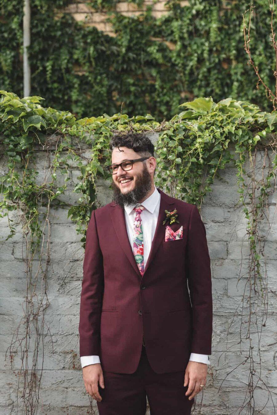 bearded groom in burgundy suit