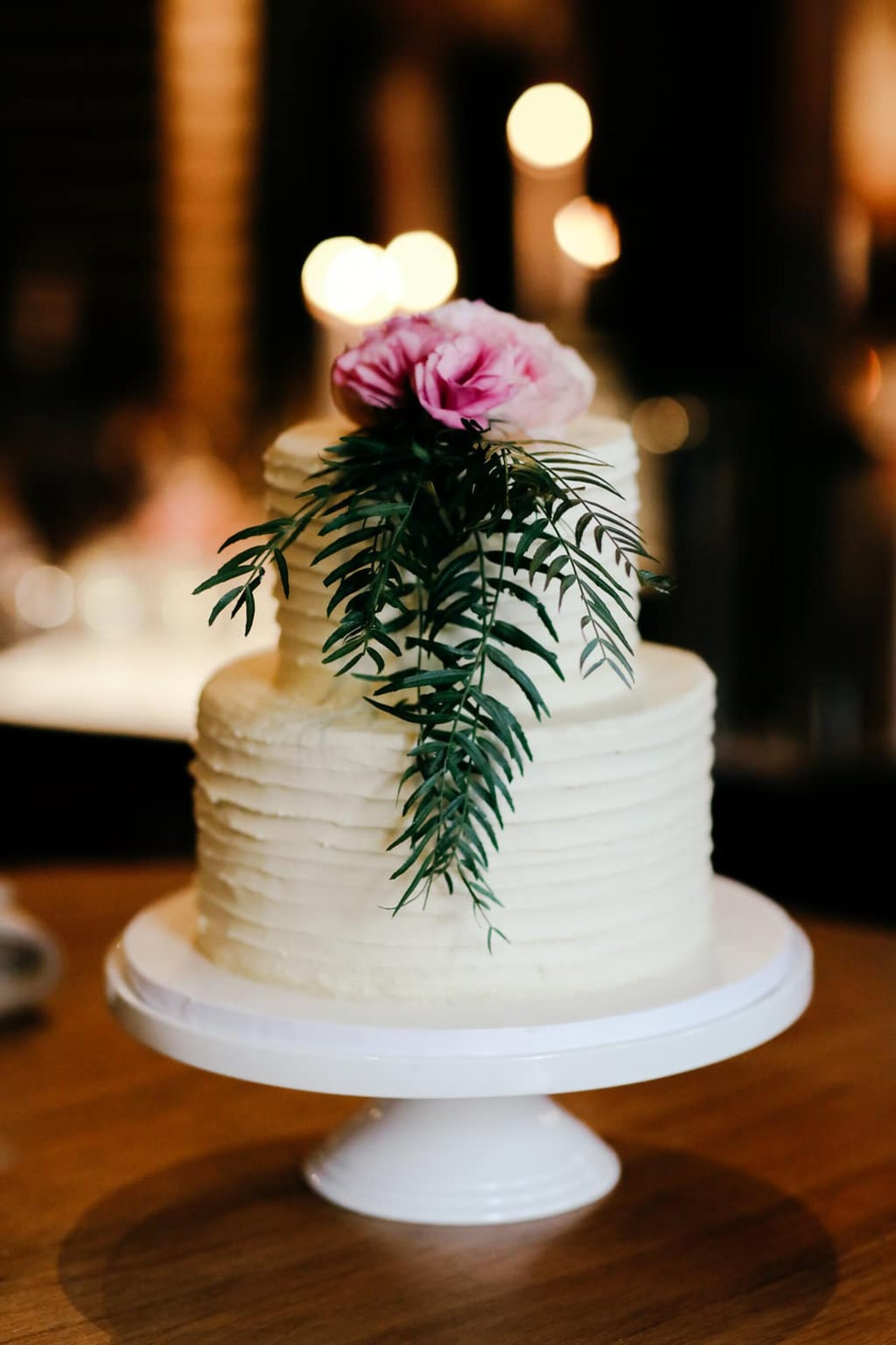 simple wedding cake with flower + foliage topper