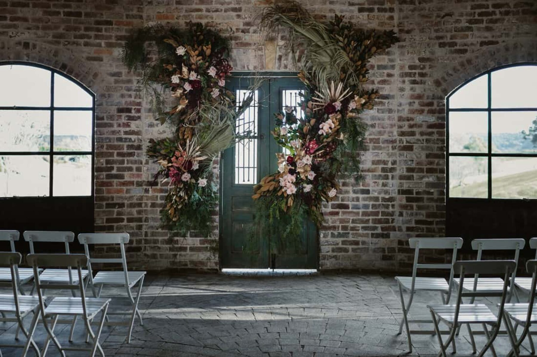 exposed brick wall with floral wedding backdrop