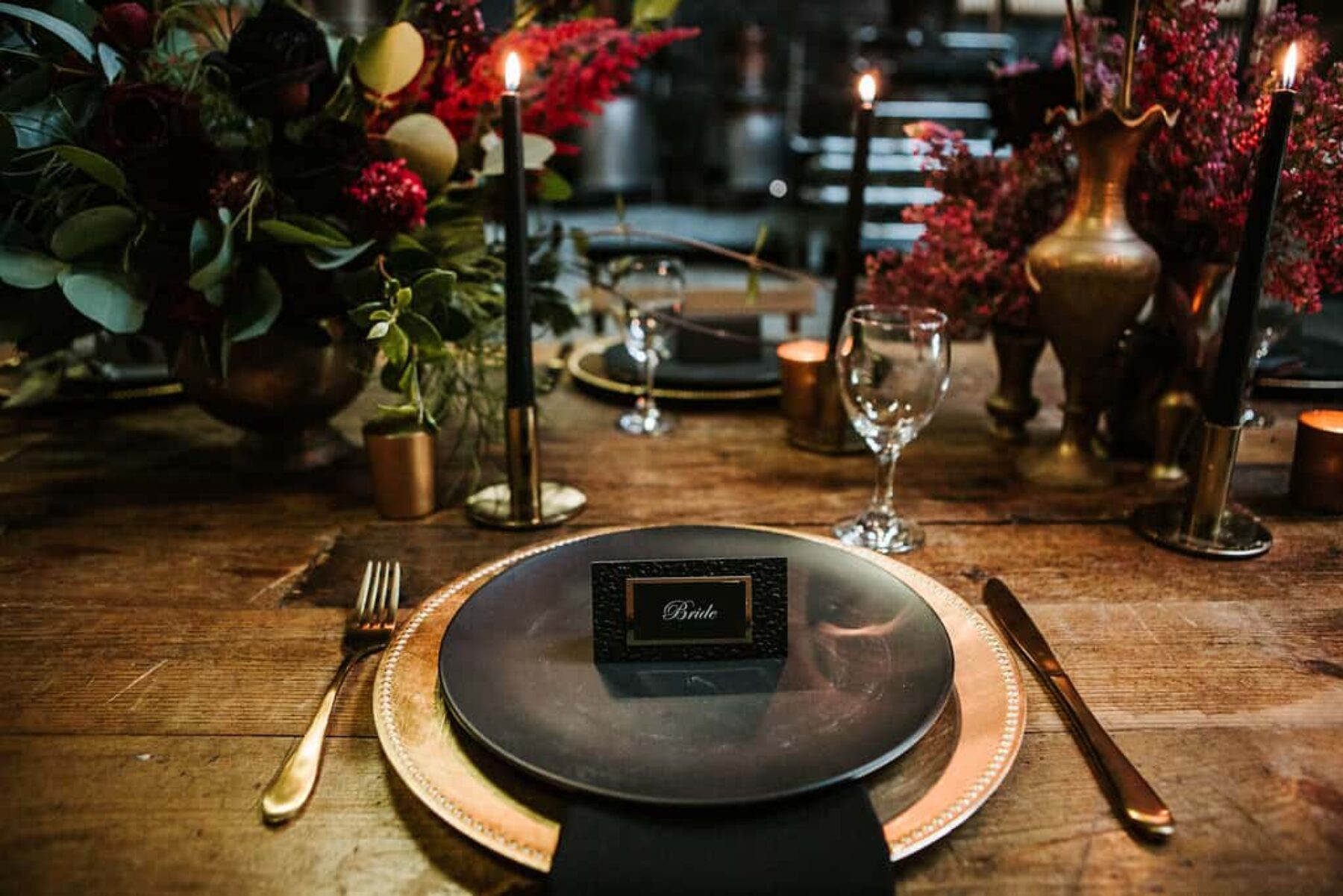 industrial wedding tablescape with black plates and gold cutlery