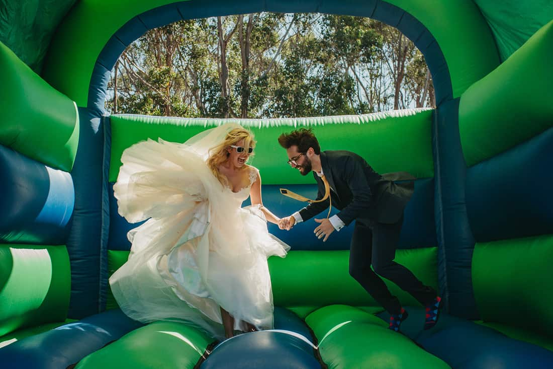 bride and groom on bouncey castle - photography by Stories by Ash