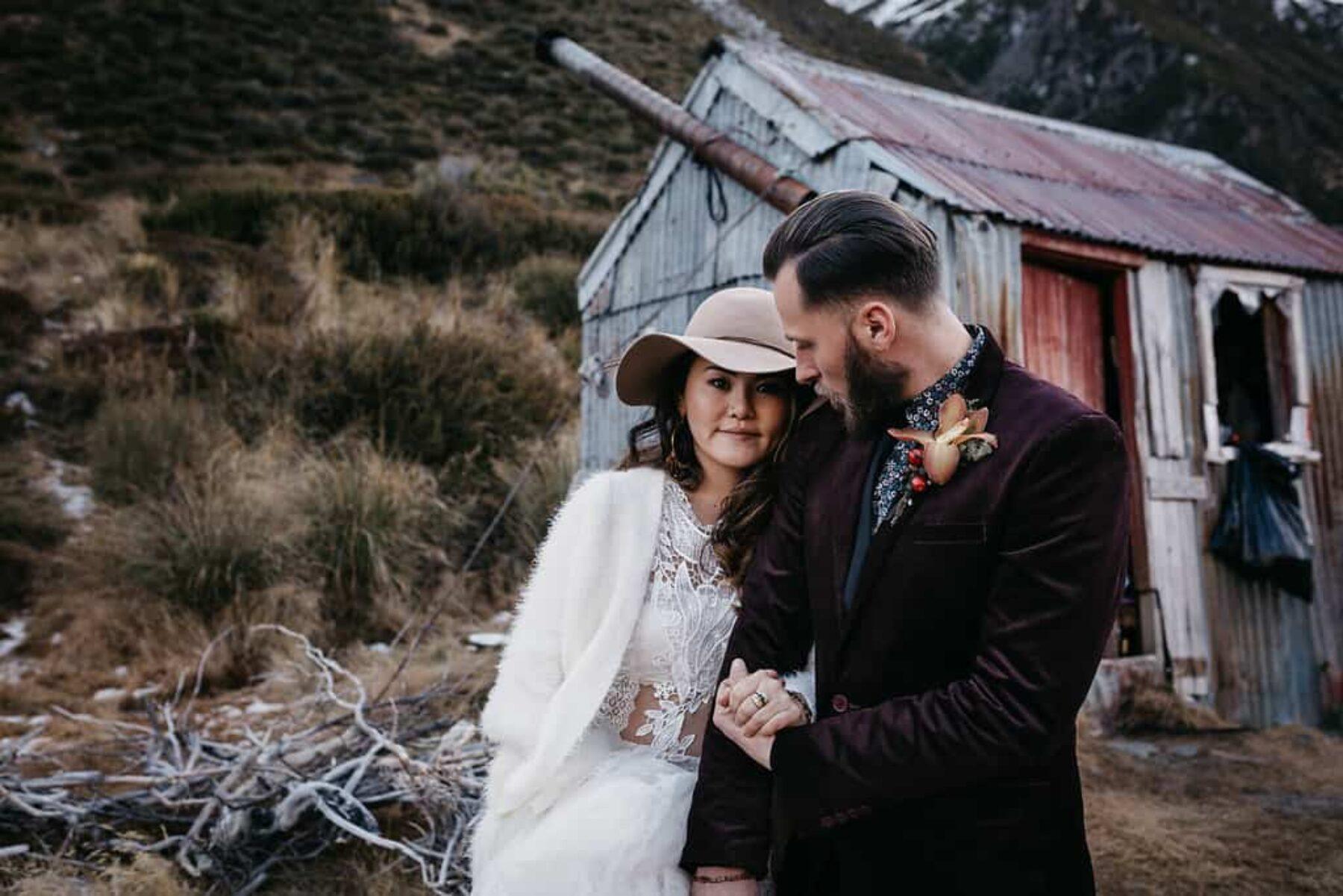 Boho bride in wide brim hat and groom in burgundy suit