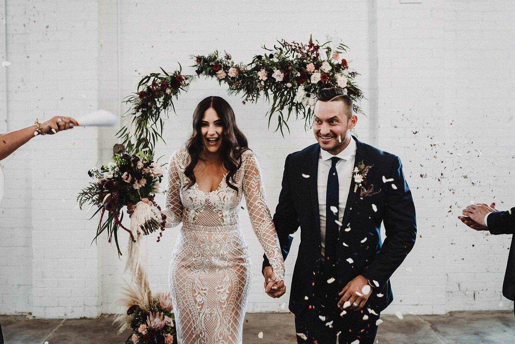 warehouse wedding with floral arch backdrop