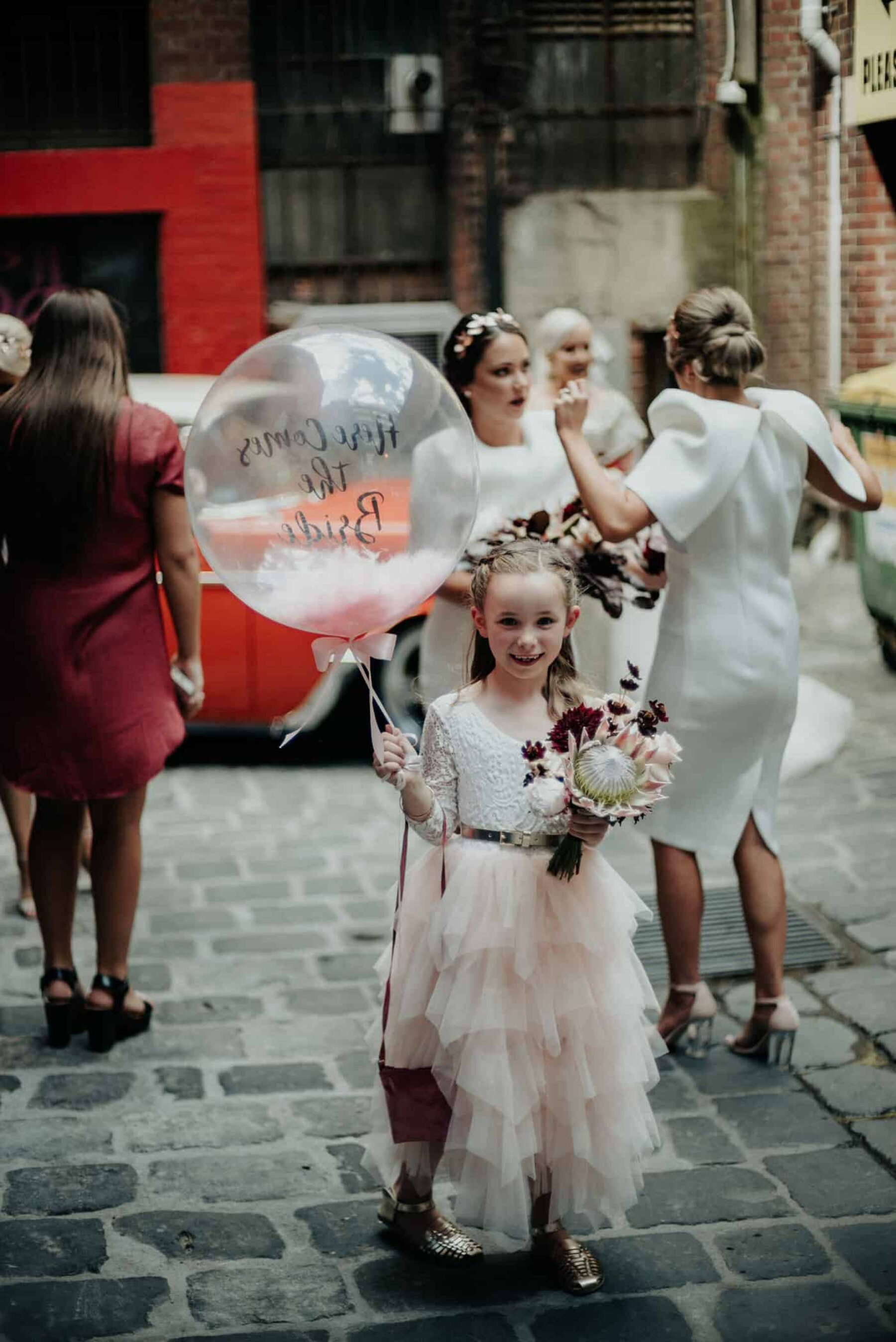 flower girl with 'here comes the bride' confetti balloon