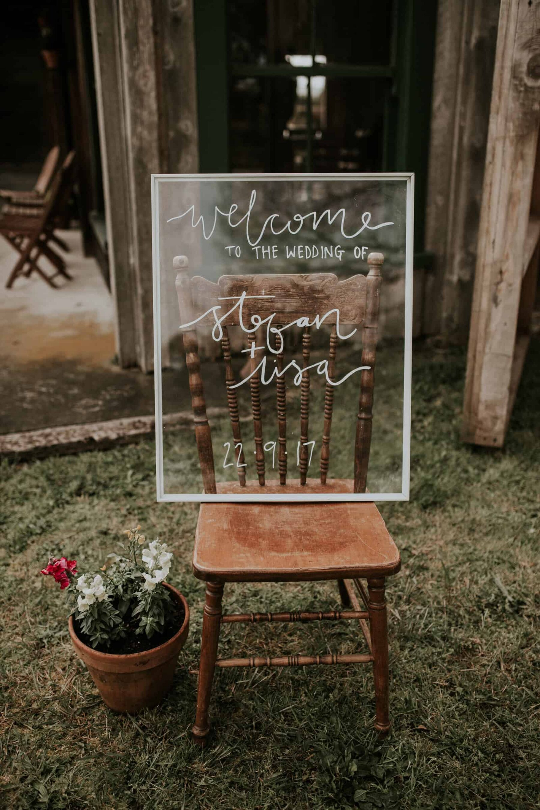 hand lettered glass wedding welcome board