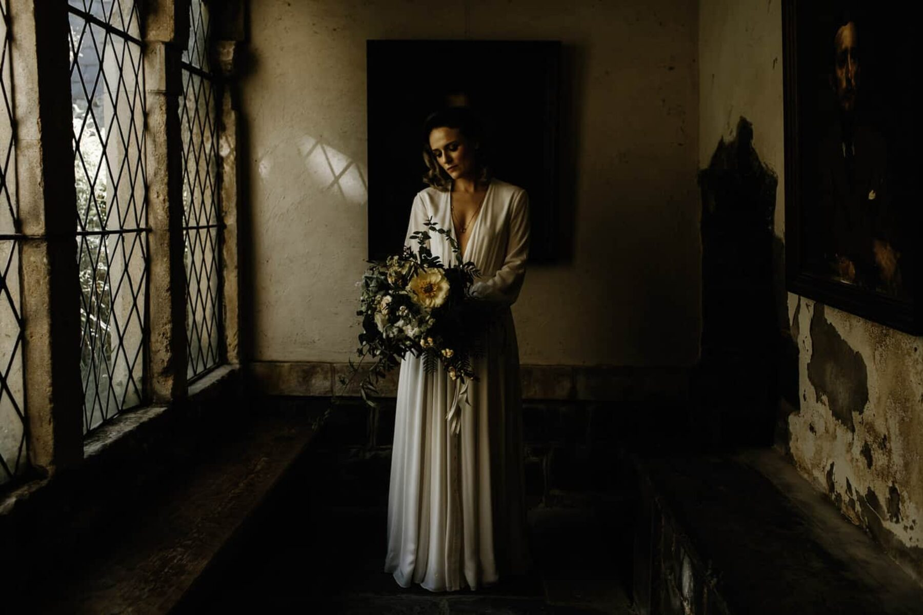 bride in robe-style wedding dress with yellow and white bouquet