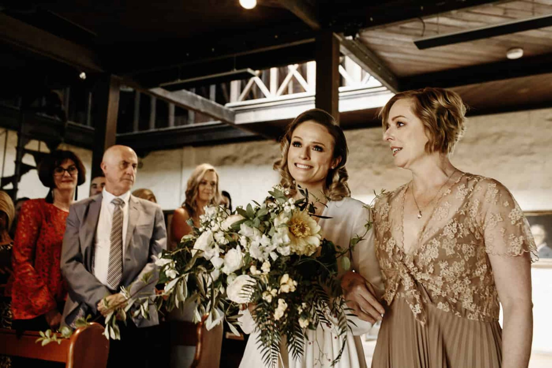 bride walking down aisle with her mum and yellow bouquet