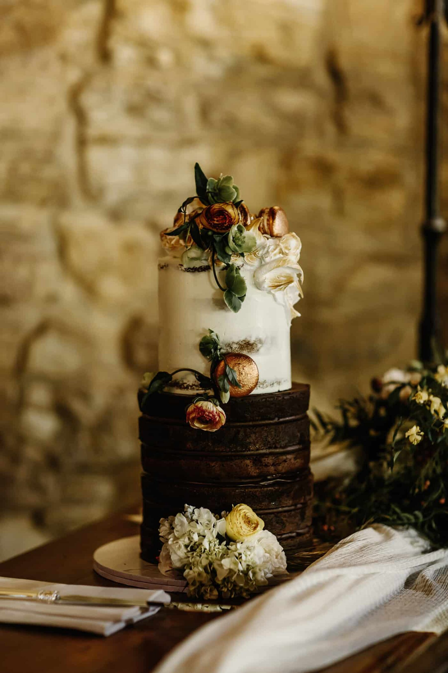 tall two-tiered naked wedding cake with rose gold macarons and fresh flowers