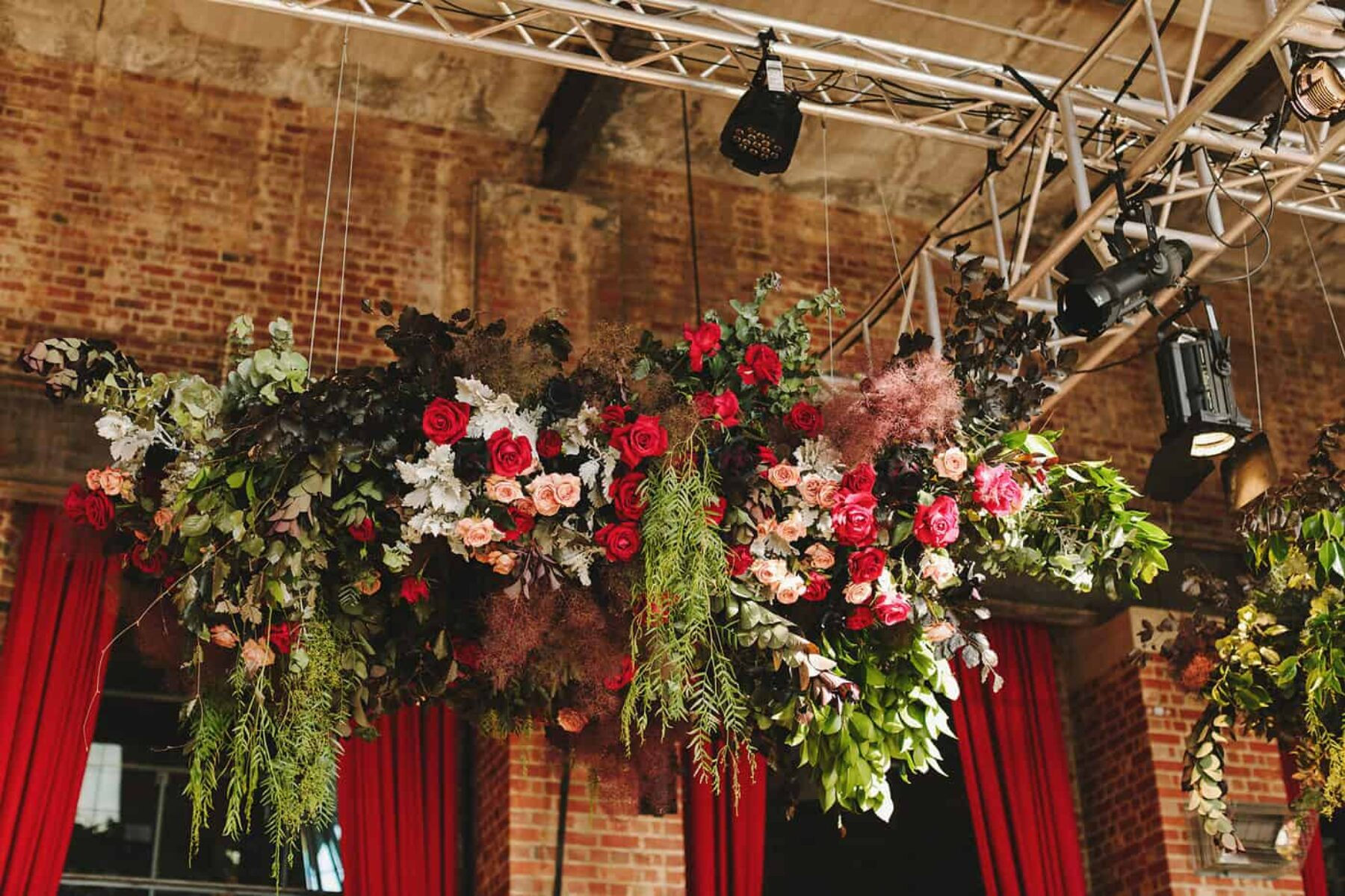 hanging floral installation in jewel tones and black roses