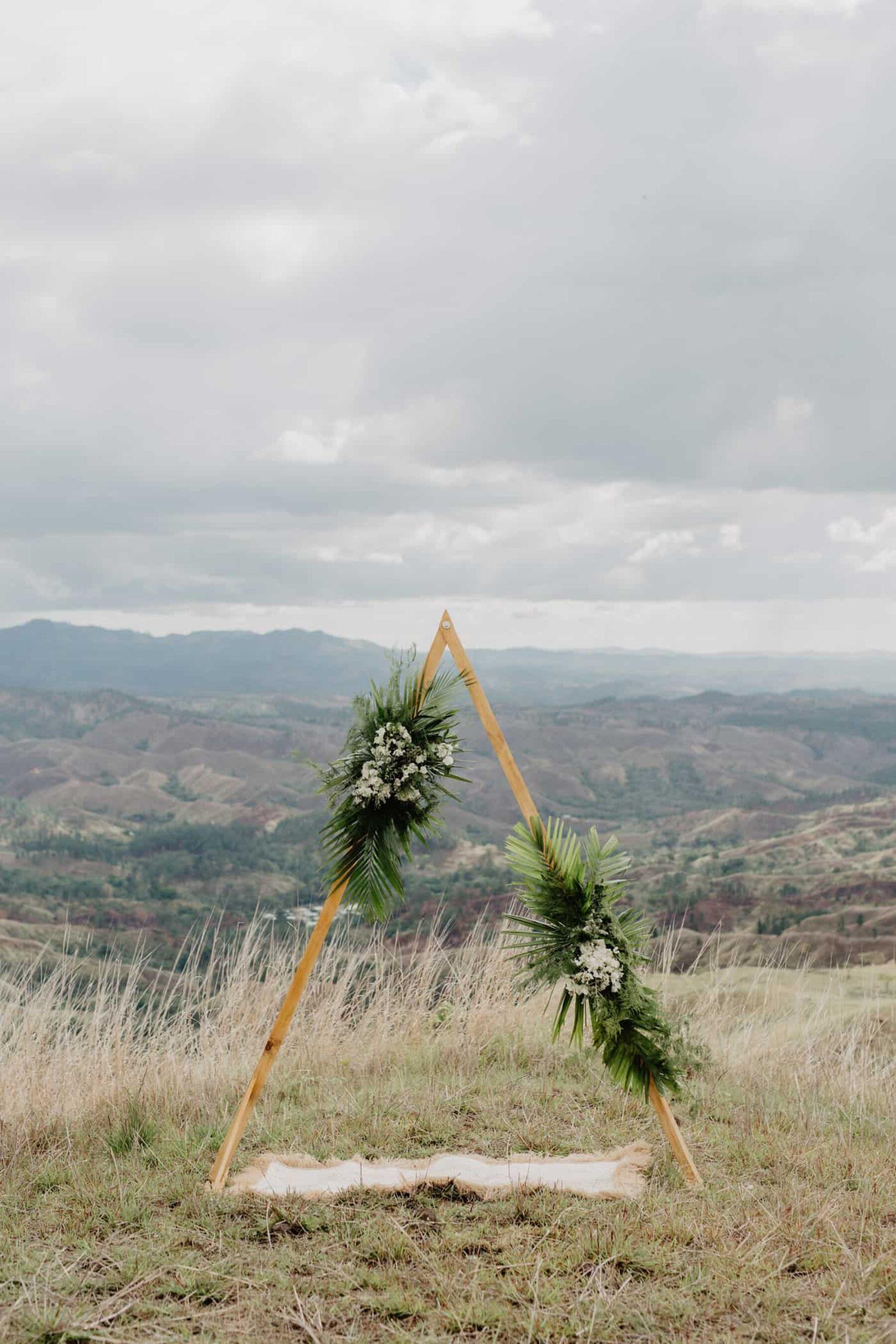 geometric triangle wedding arbour with tropical greenery