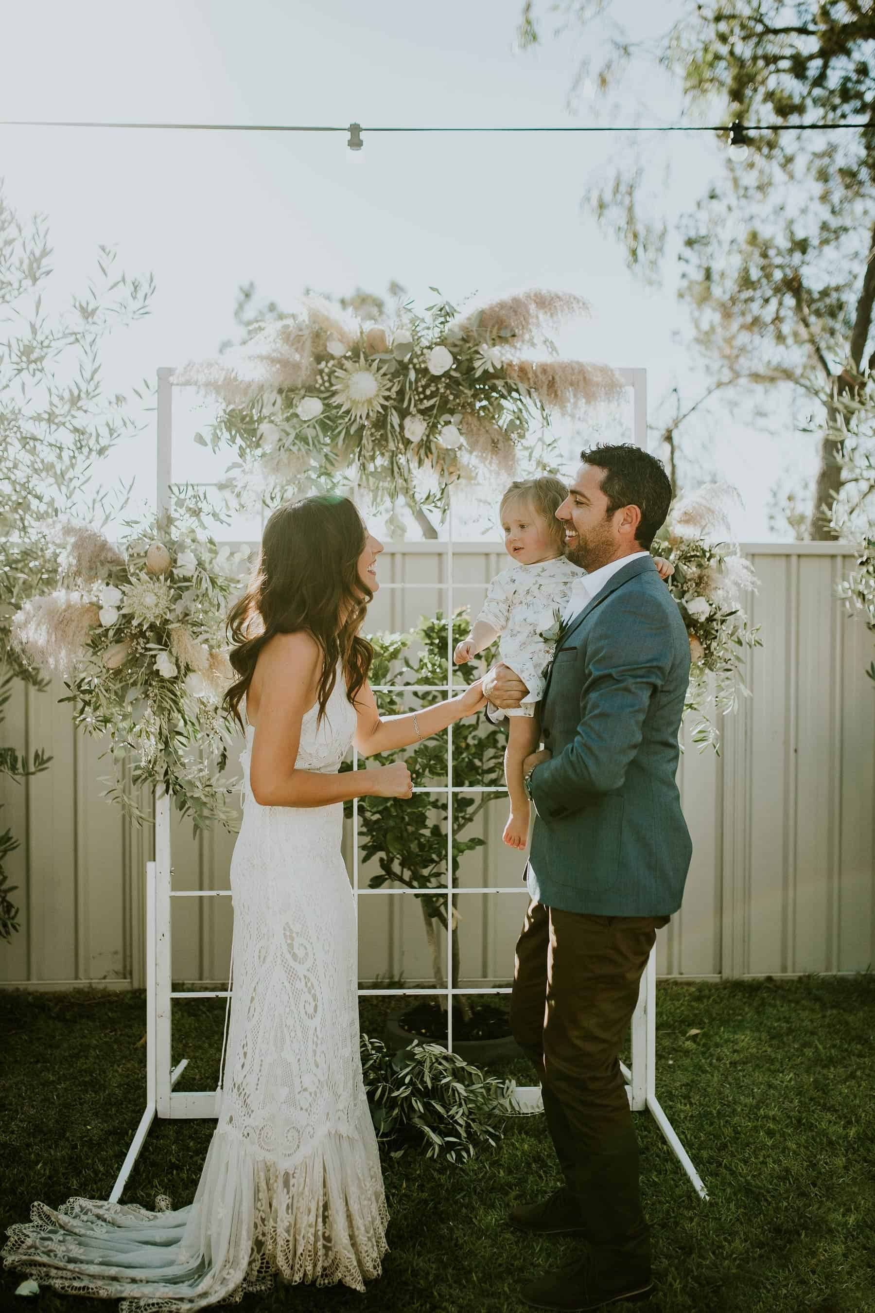 backyard wedding with white floral arbour