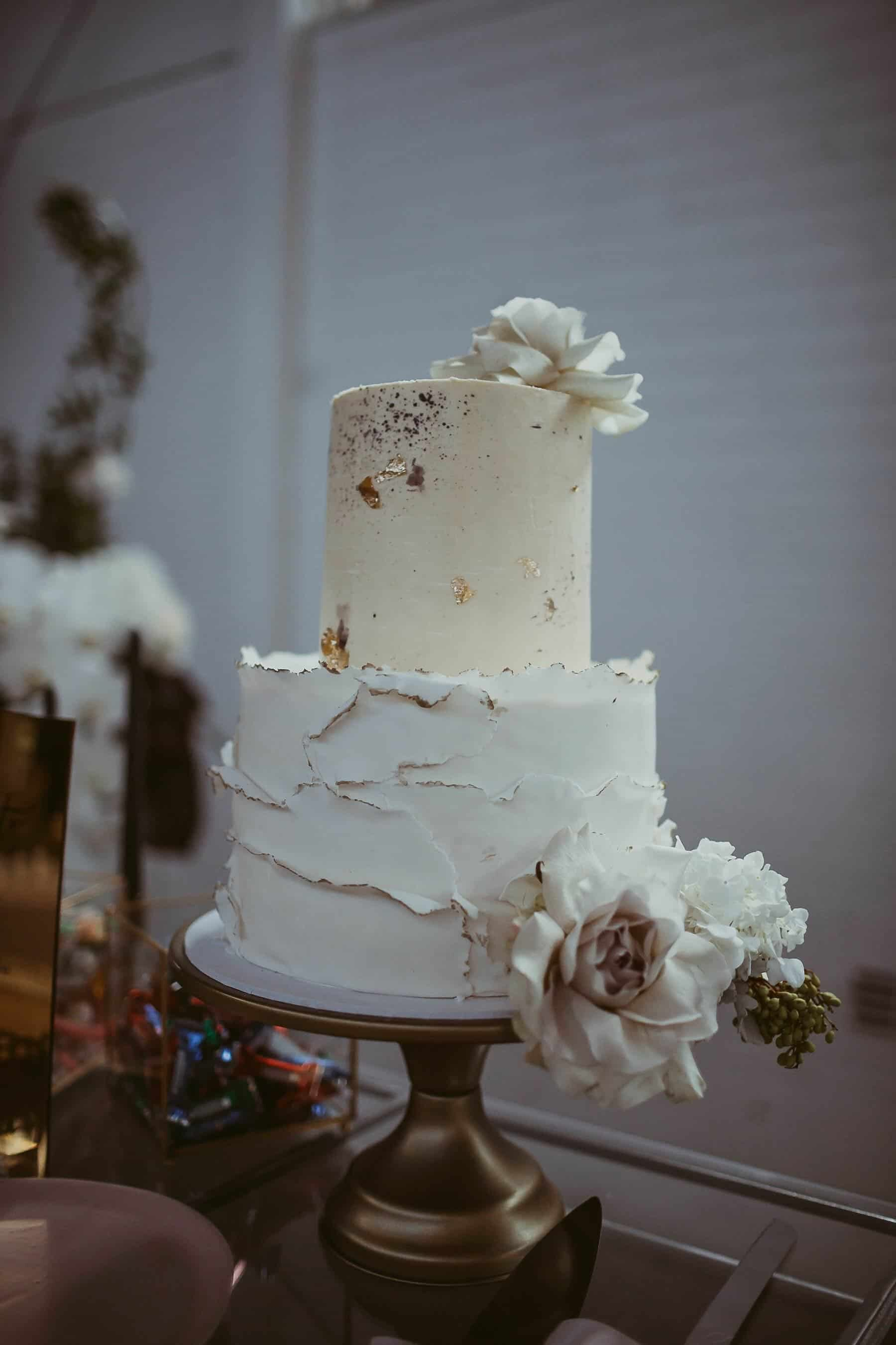 white two tier wedding cake with gold leaf