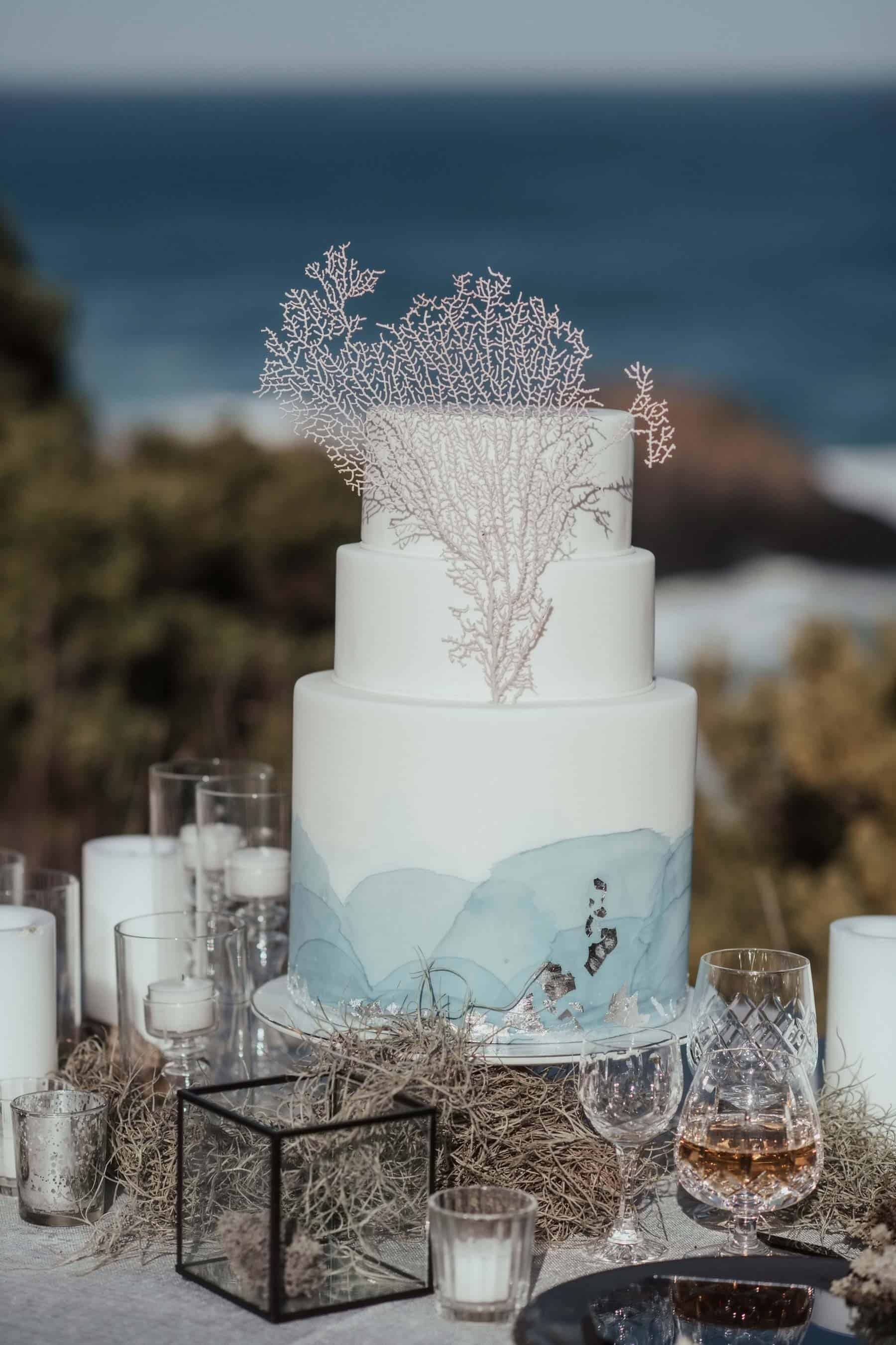 oceanic watercolour wedding cake with coral topper
