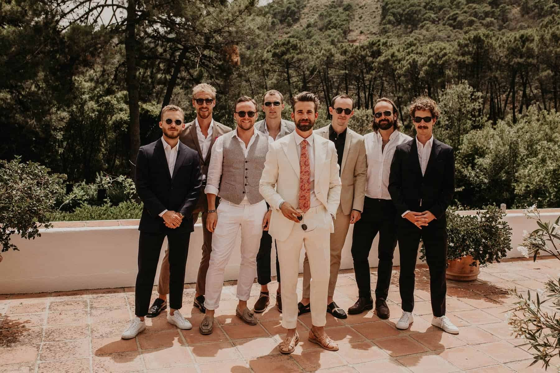 groom in white suit and mismatched groomsmen