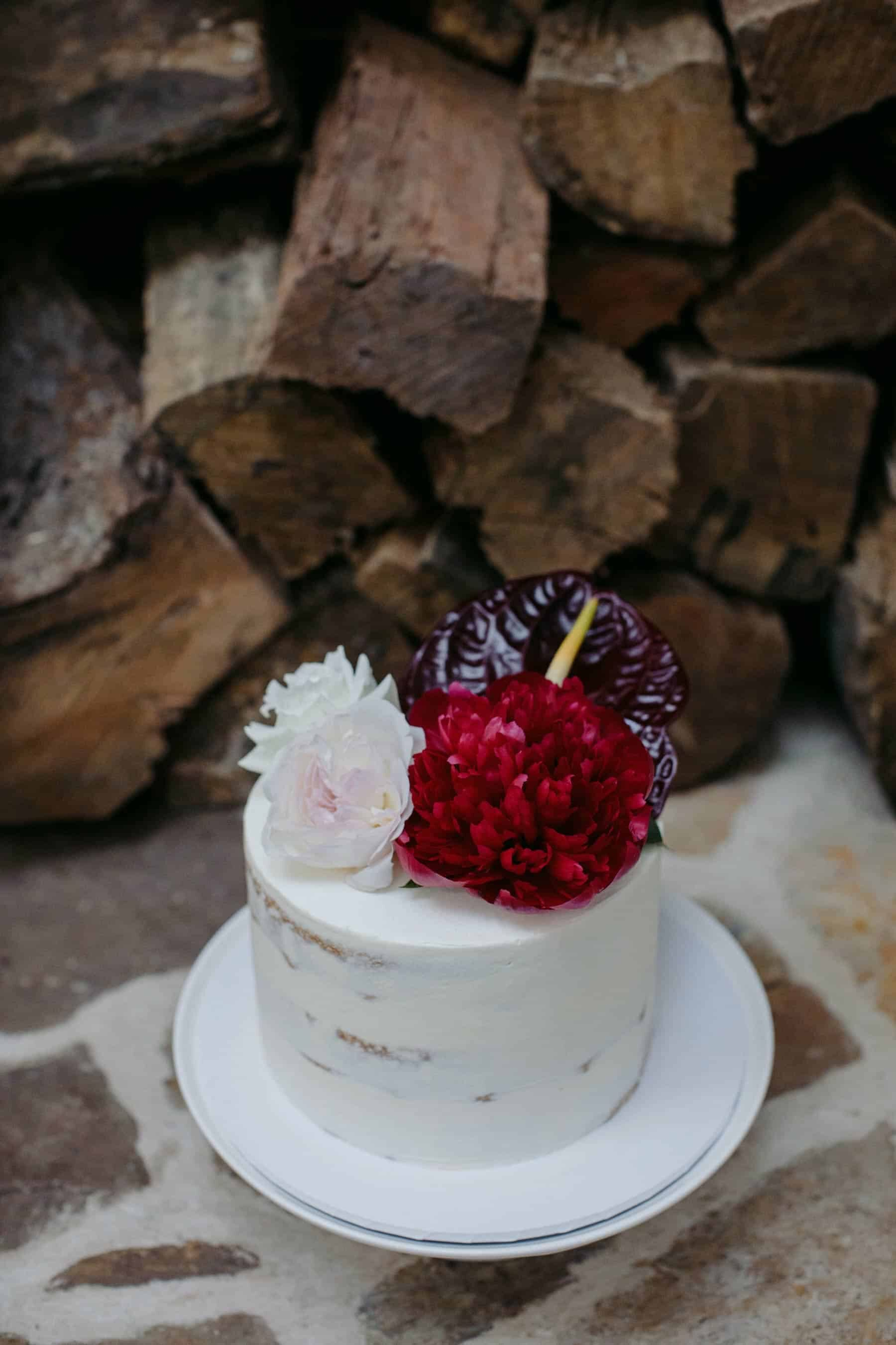simple white cake with blush and burgundy flowers