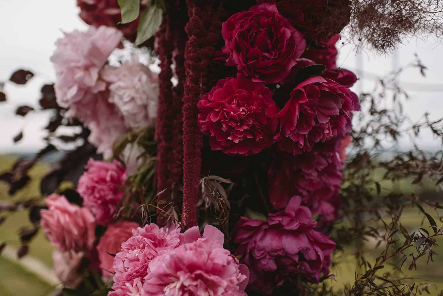 wire wedding arbour with pink and burgundy flowers