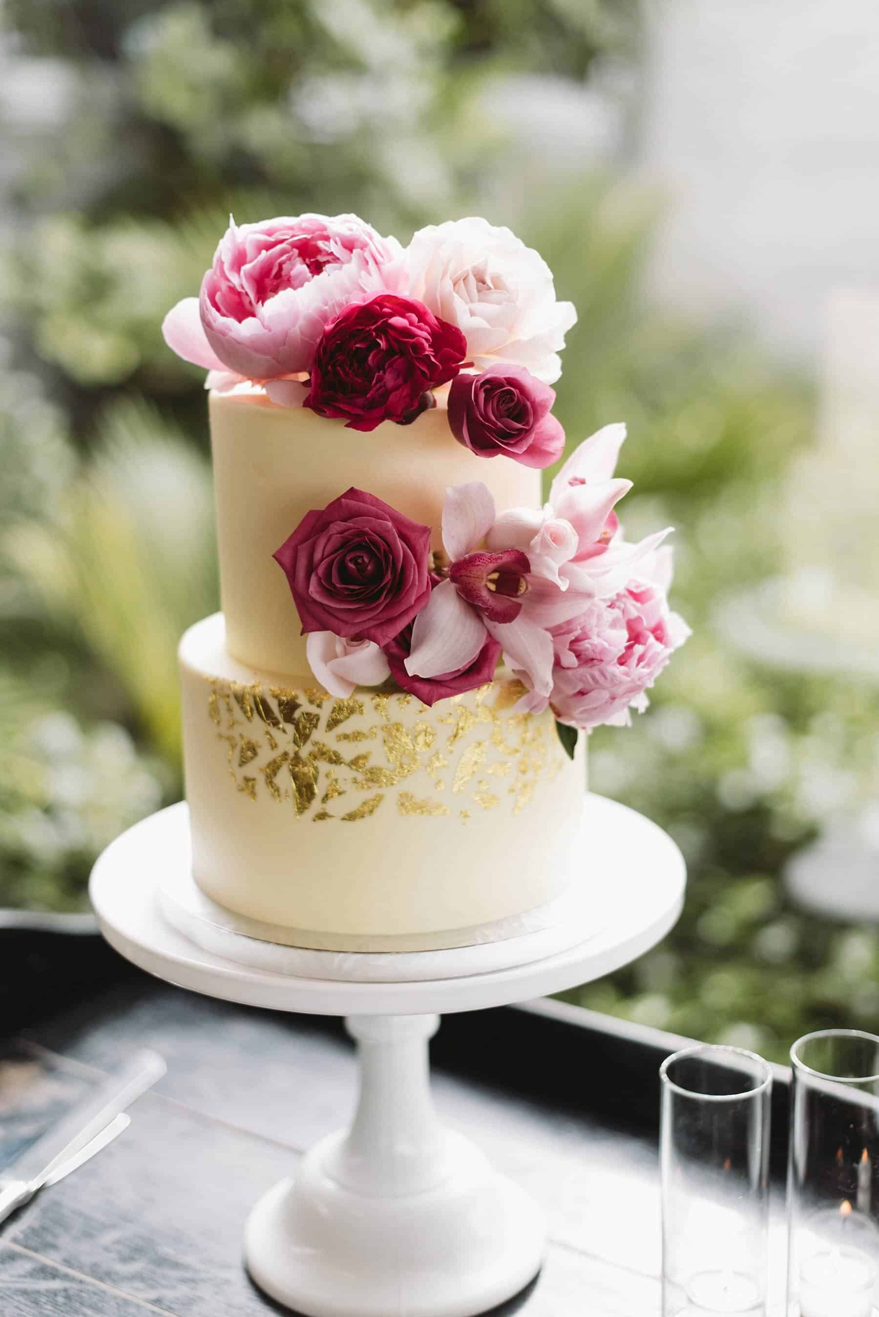 simple white gold-flecked wedding cake with pink flowers