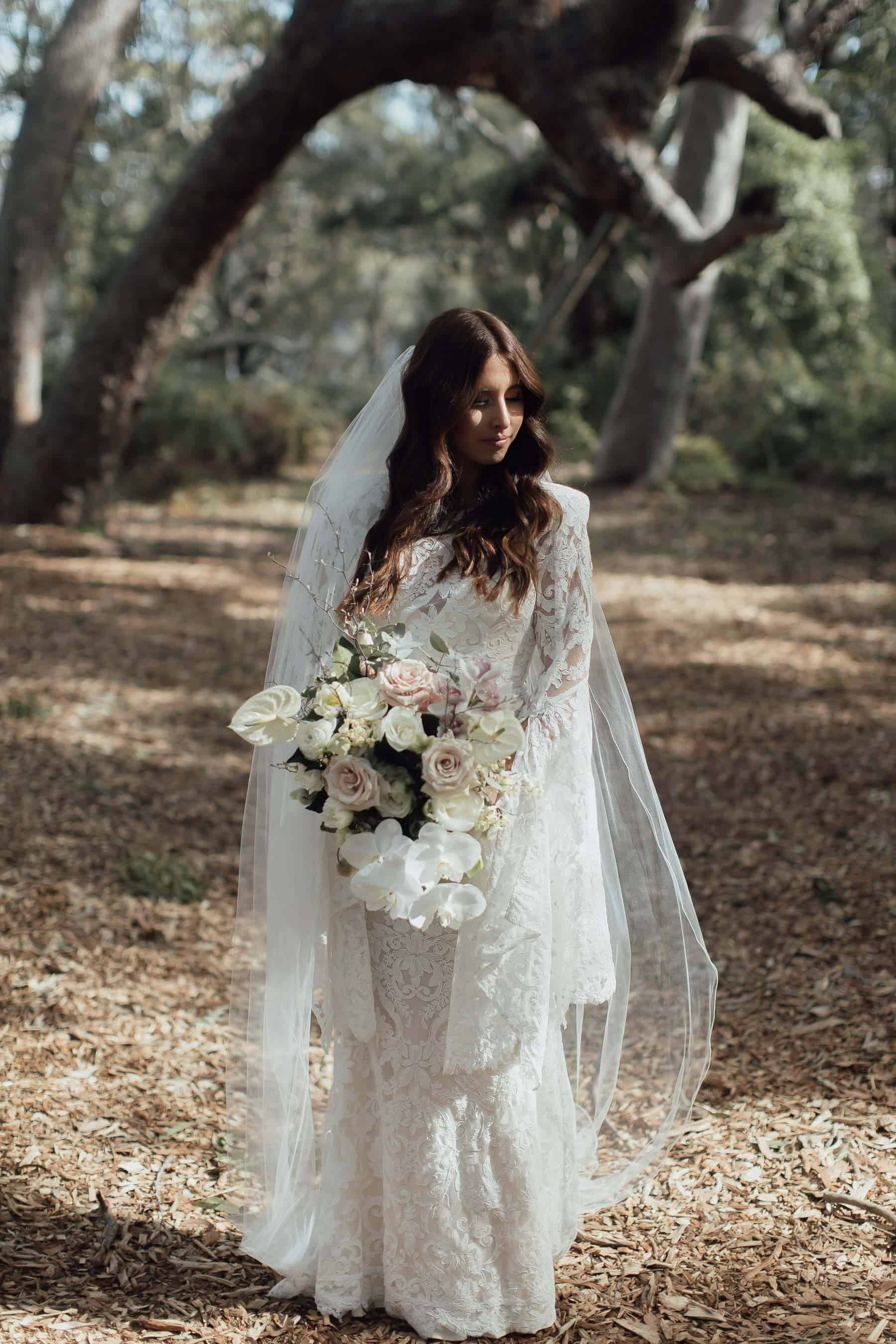 pregnant bride in bell sleeve lace wedding dress by Alex Perry