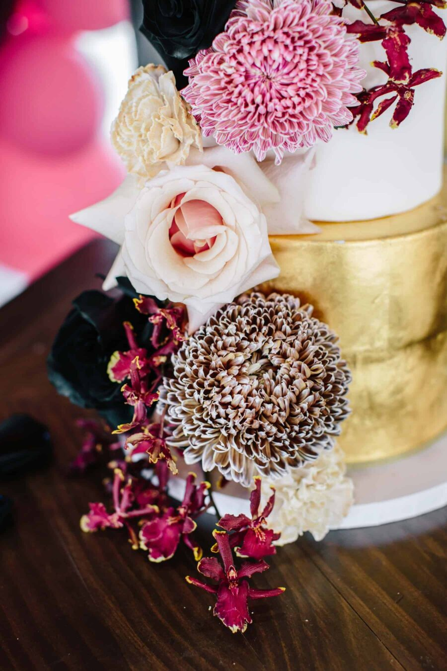 gold wedding cake with blush and burgundy flowers