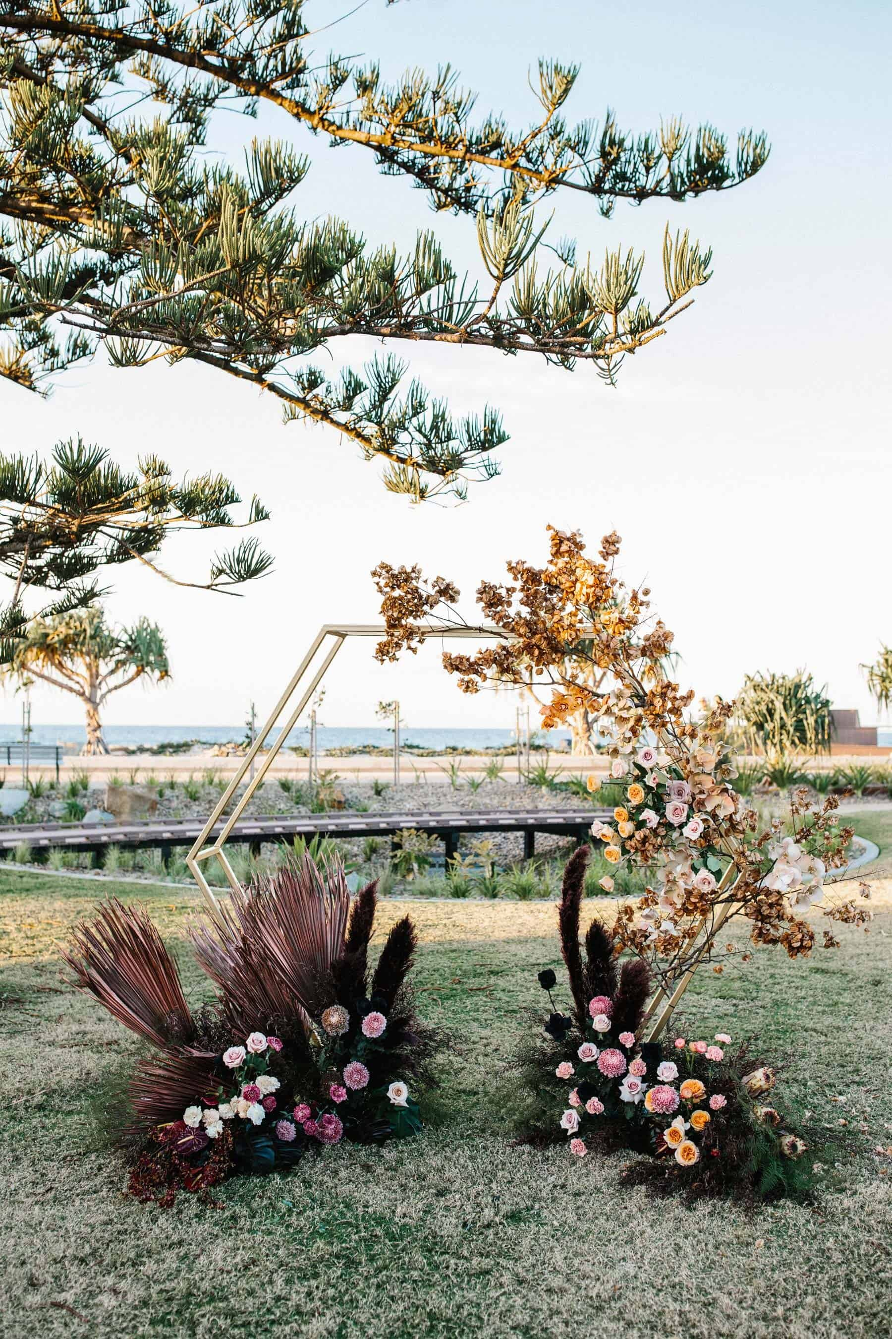 hexagonal wedding arbour with blush and burgundy florals