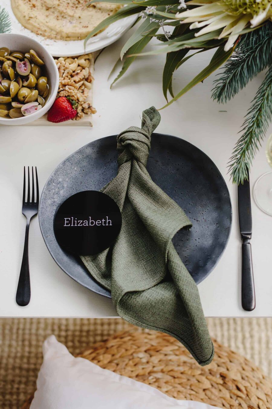 tied linen napkin on black plate with round acrylic place card
