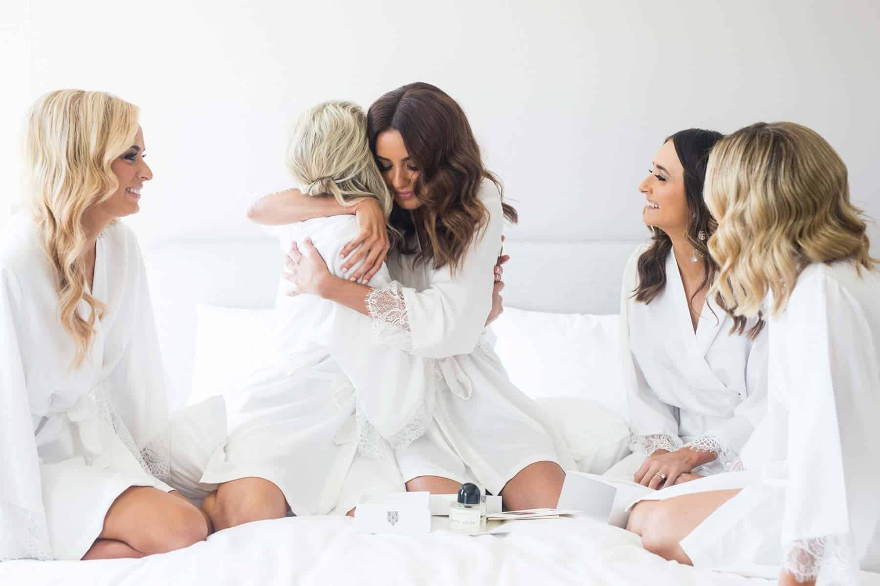 bride and bridesmaids getting ready in white robes