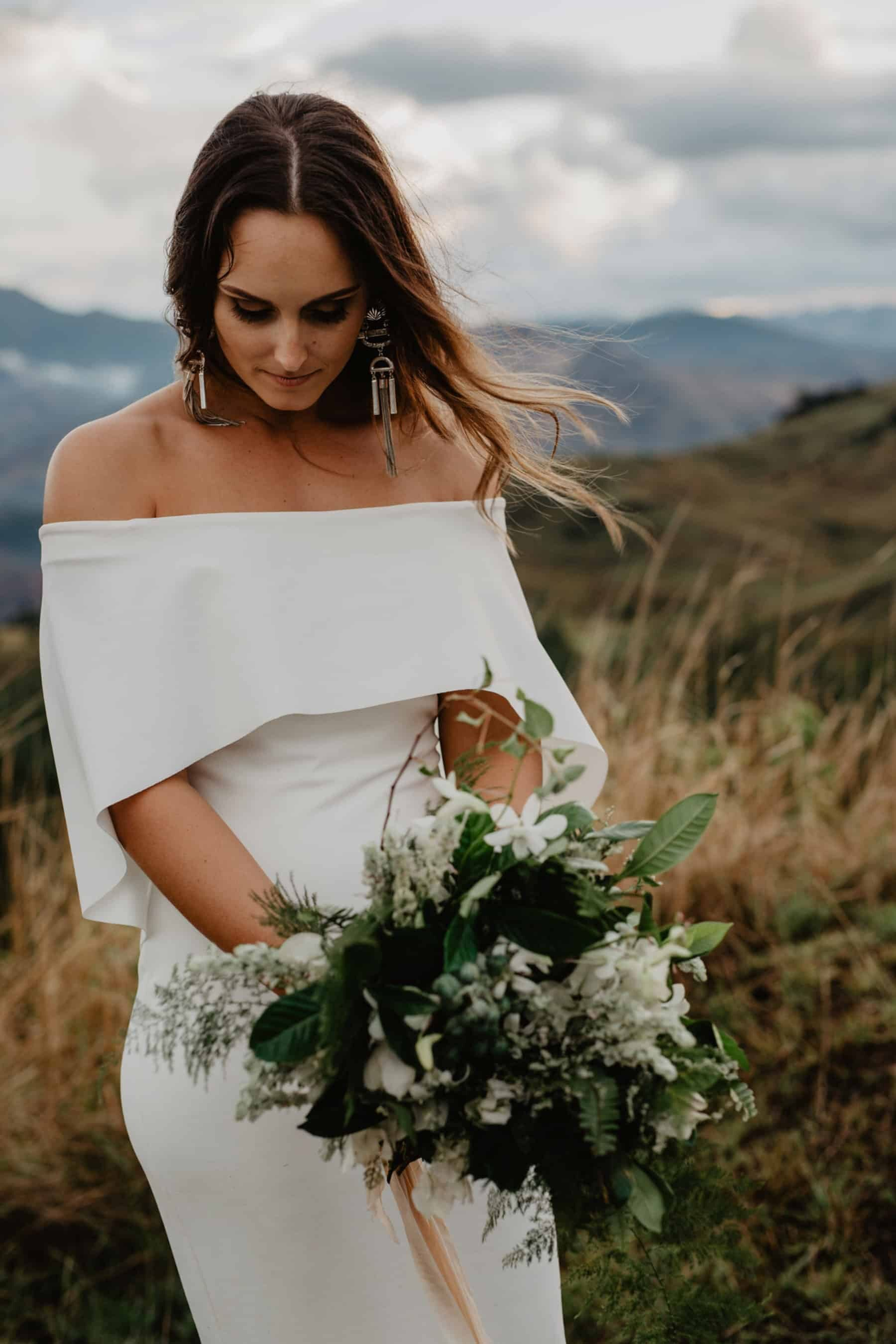 modern and minimal wedding dress with off-shoulder cape detail