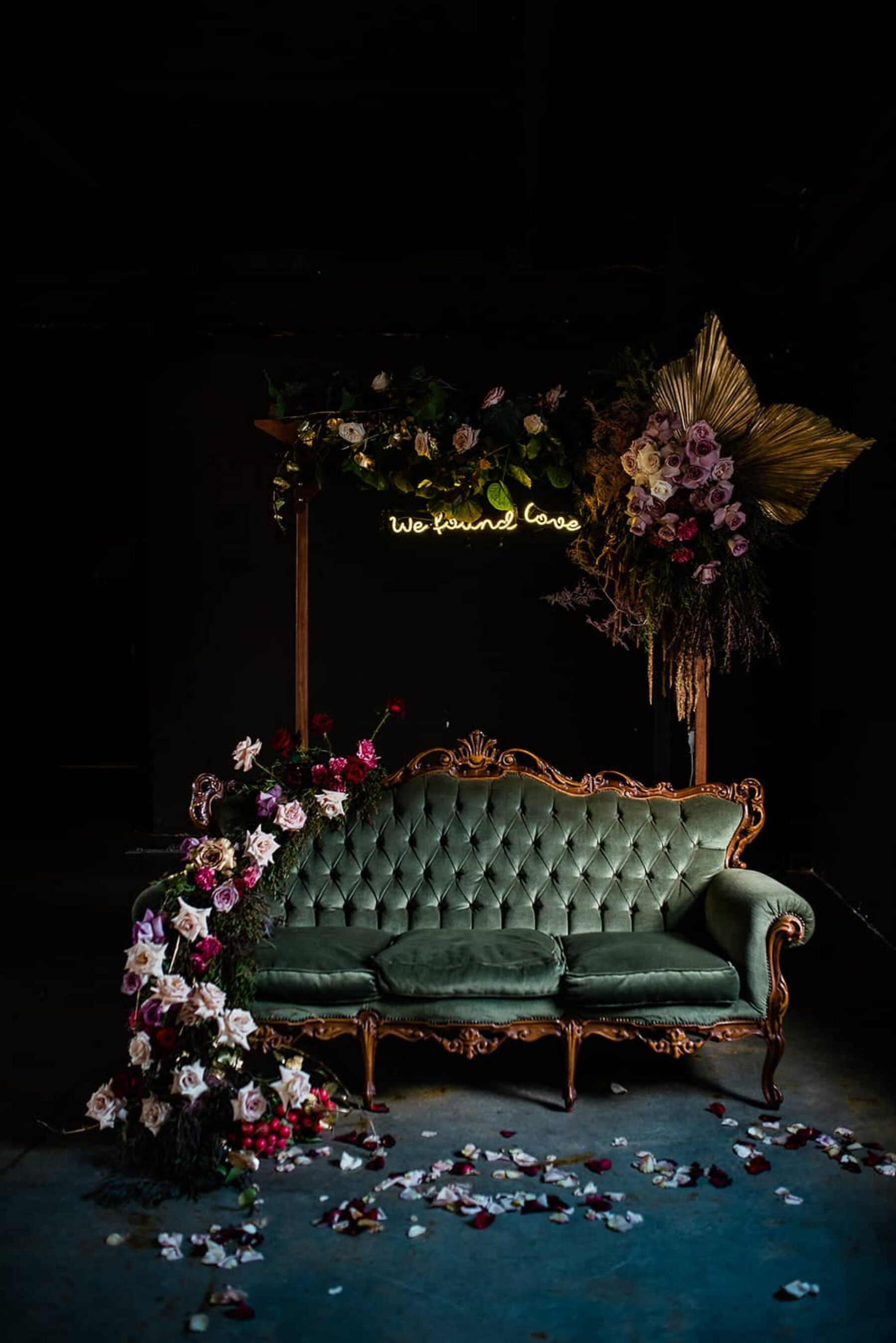 vintage green velvet couch with floral installation