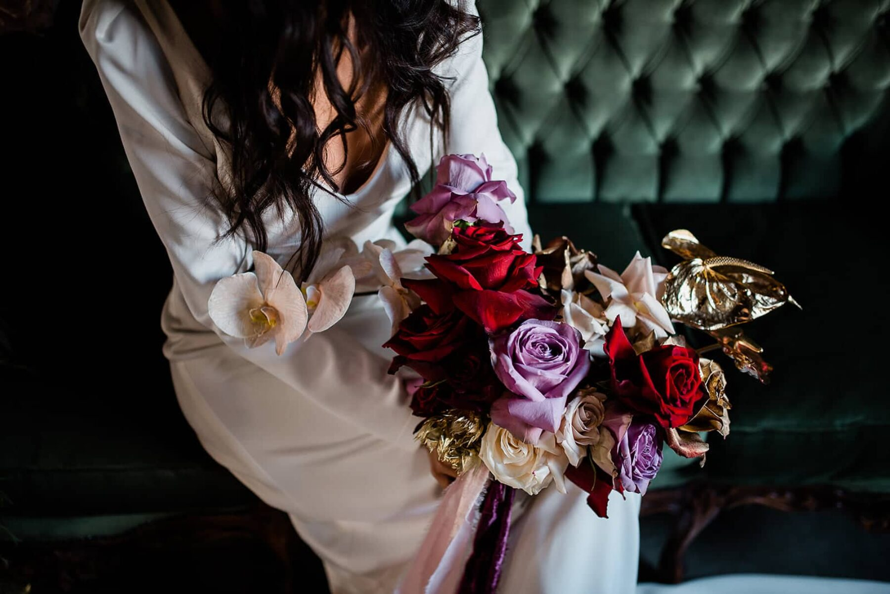 red and purple bridal bouquet with gold painted roses