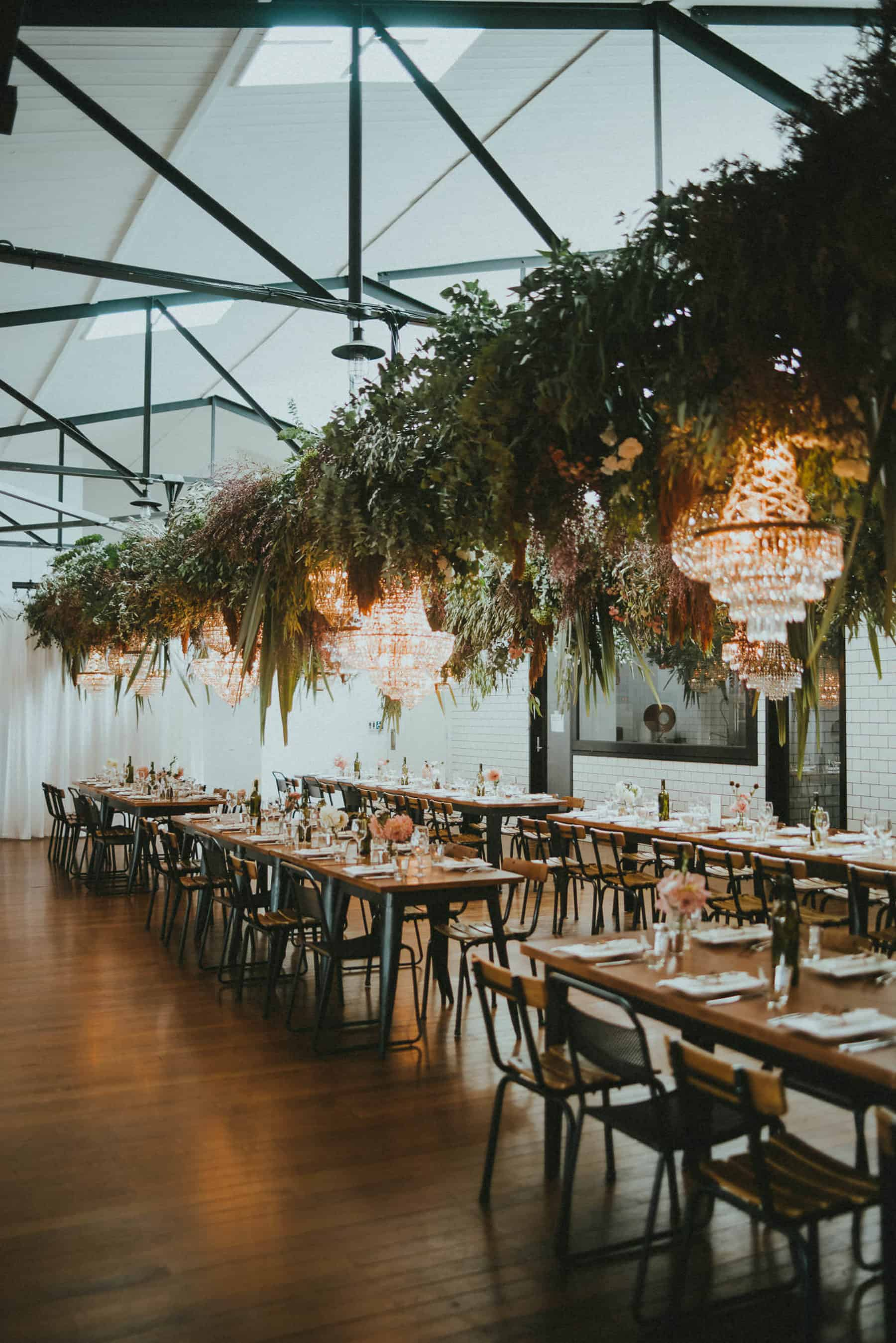 Hanging floral and foliage installations with chandeliers