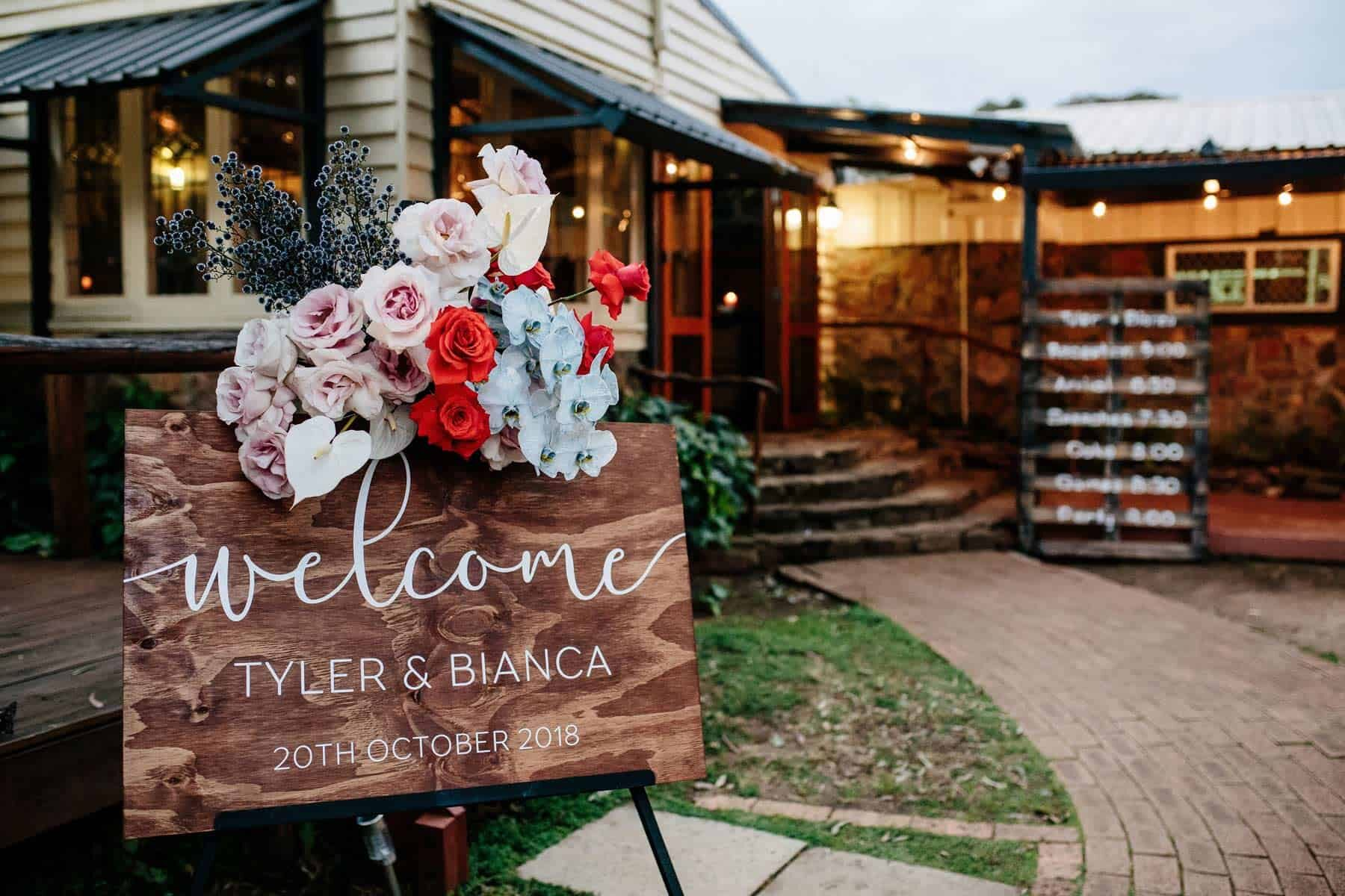Wooden welcome sign with colourful roses