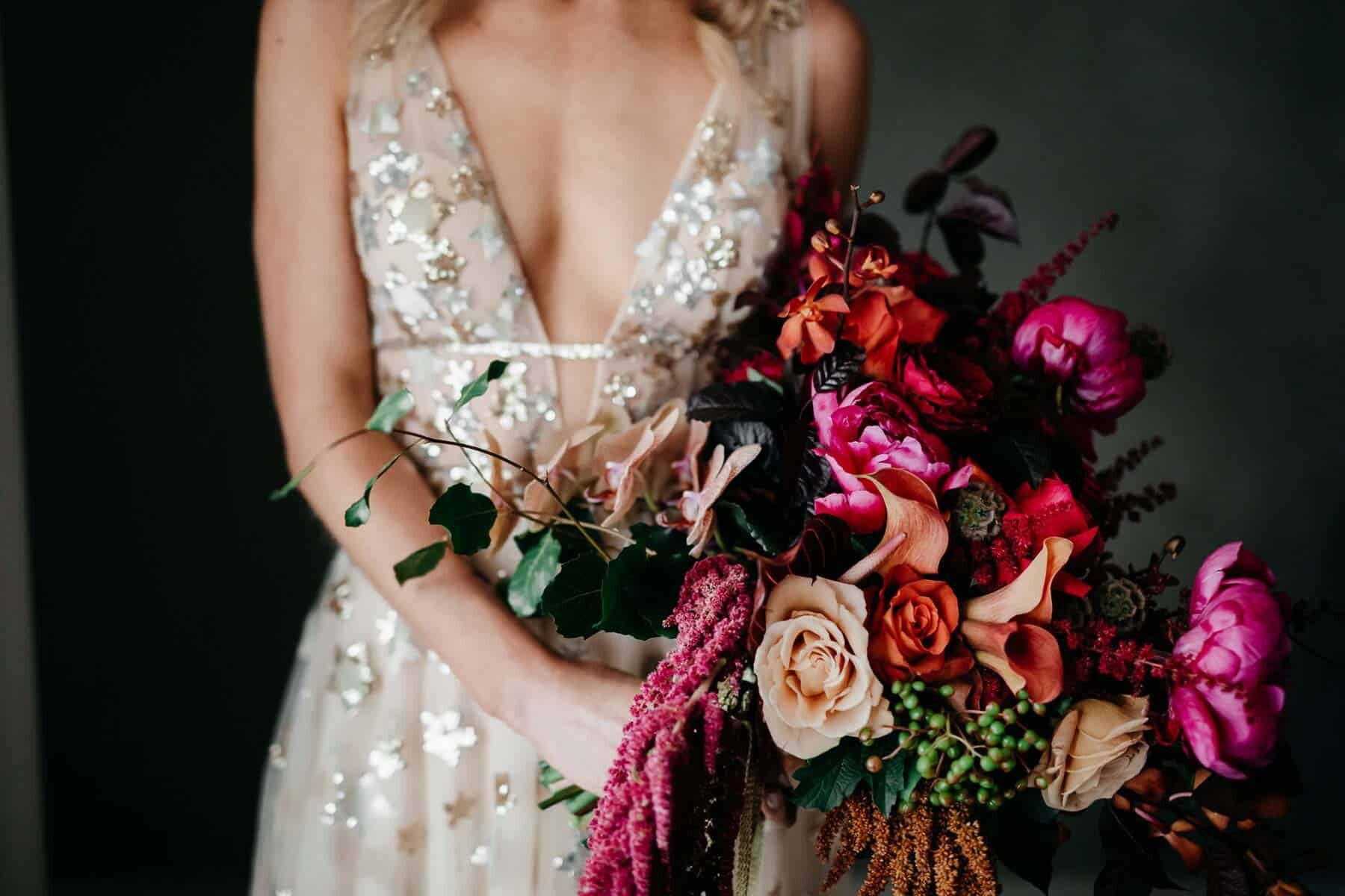 bride wears gold willowby by watters with gold amaroq crown and vibrant pink bouquet