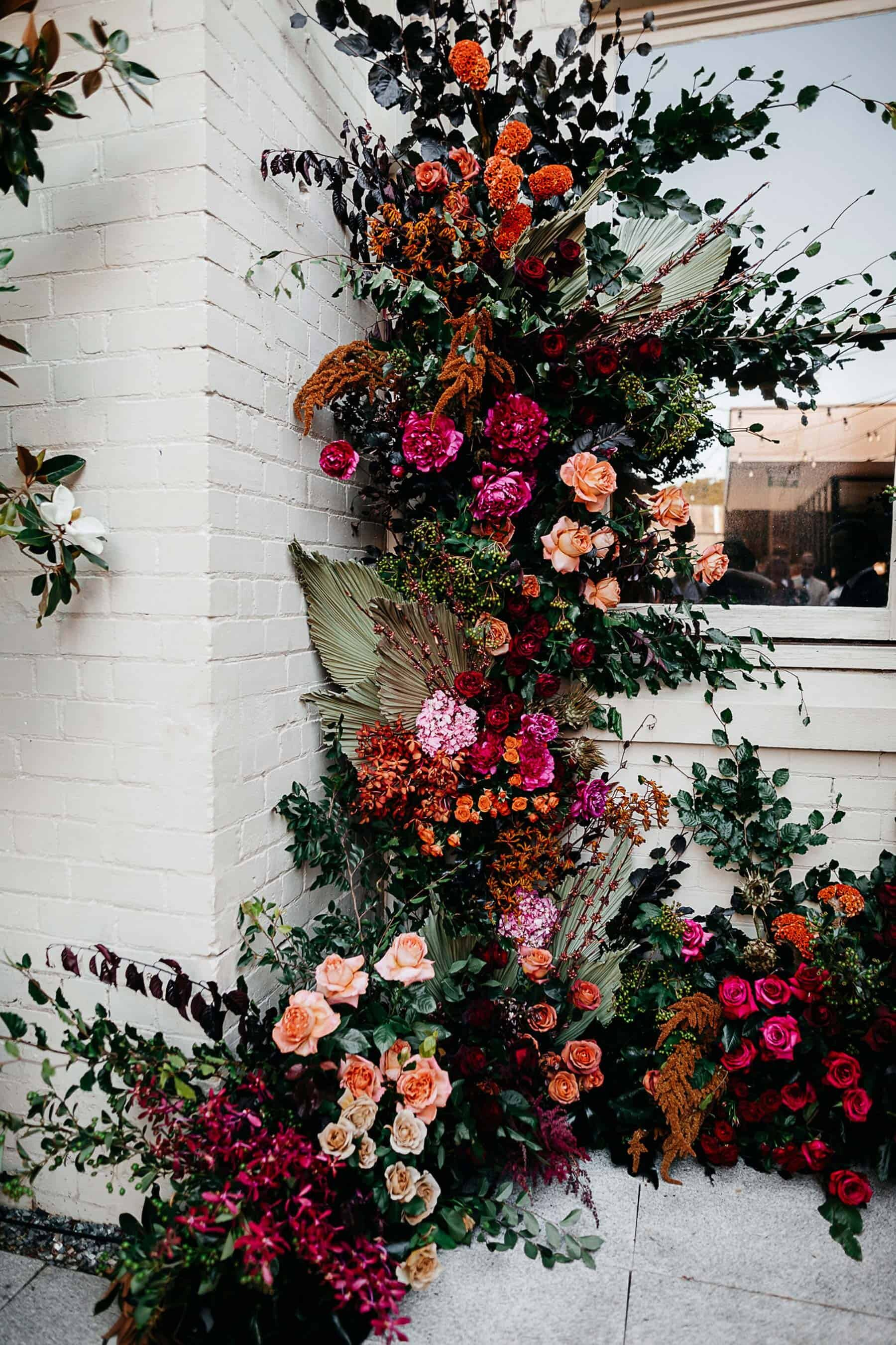 Vibrant climbing flower wall for wedding ceremony