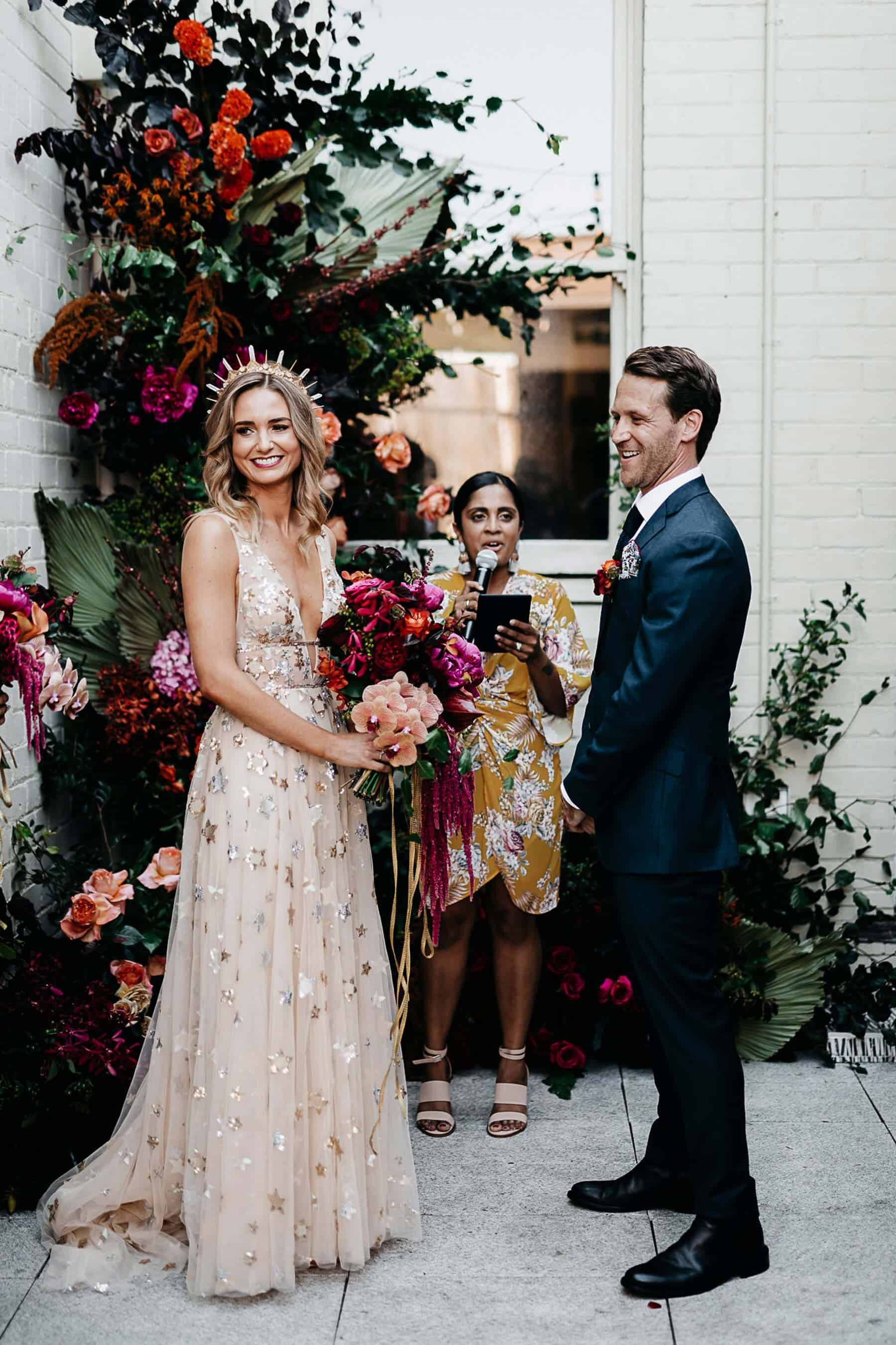 Bride wears gold Willowby wedding dress and amaroq crown with vibrant pink and red bouquet