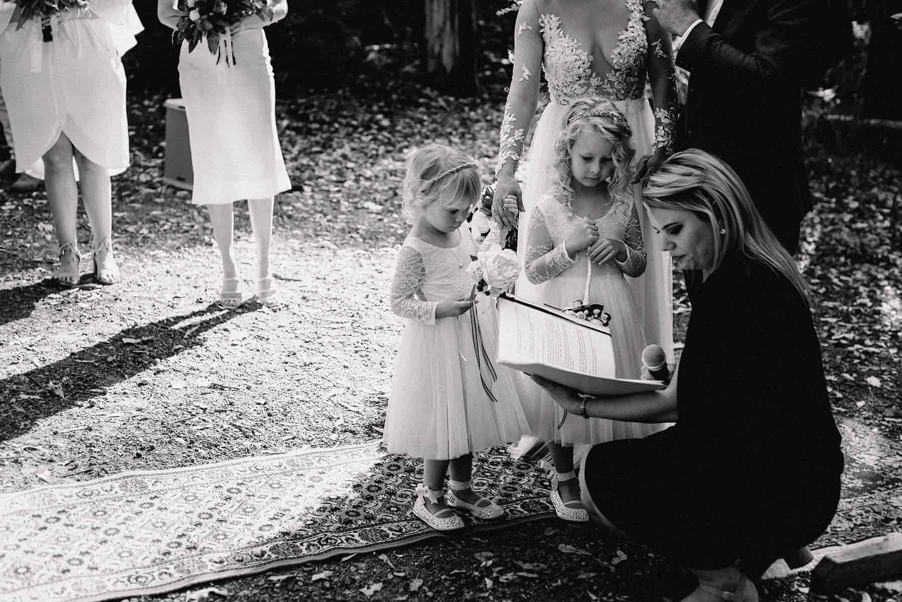Celebrant includes flower girls in ceremony at rustic forest wedding