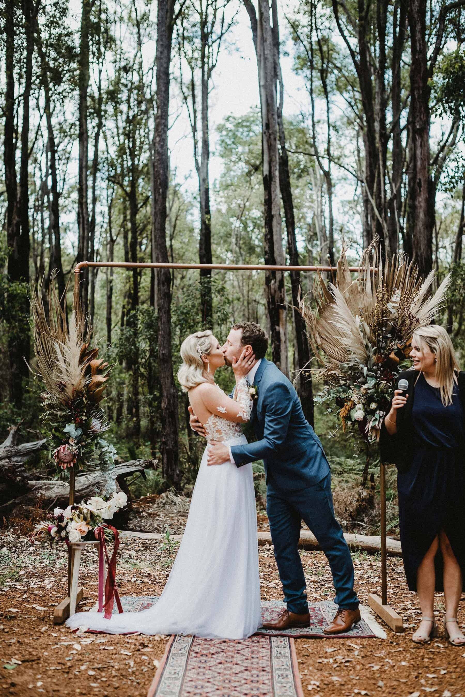 Paula & Jo bridal gown with groom's navy suit in forest wedding