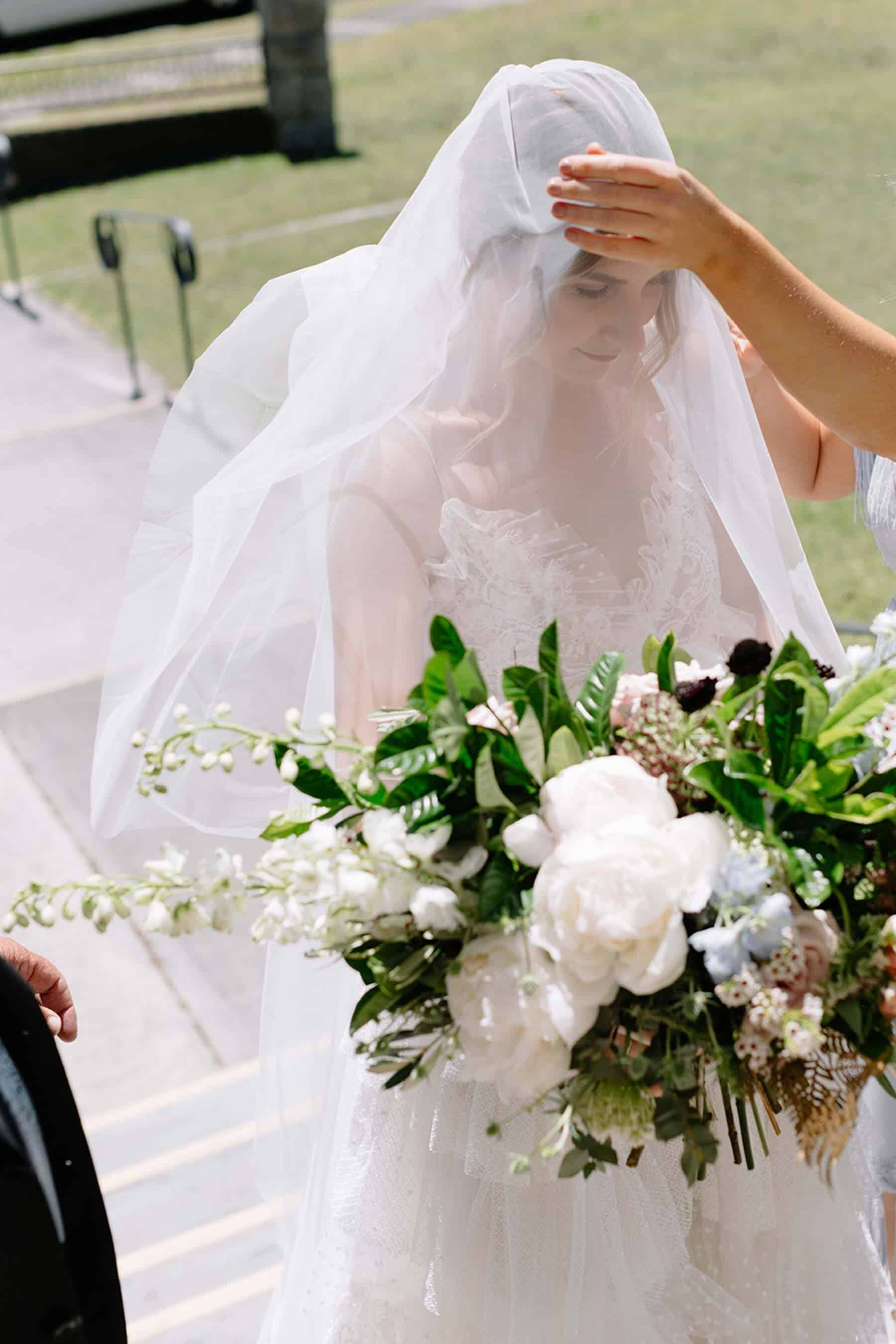 bride with unstructured green and white bridal bouquet