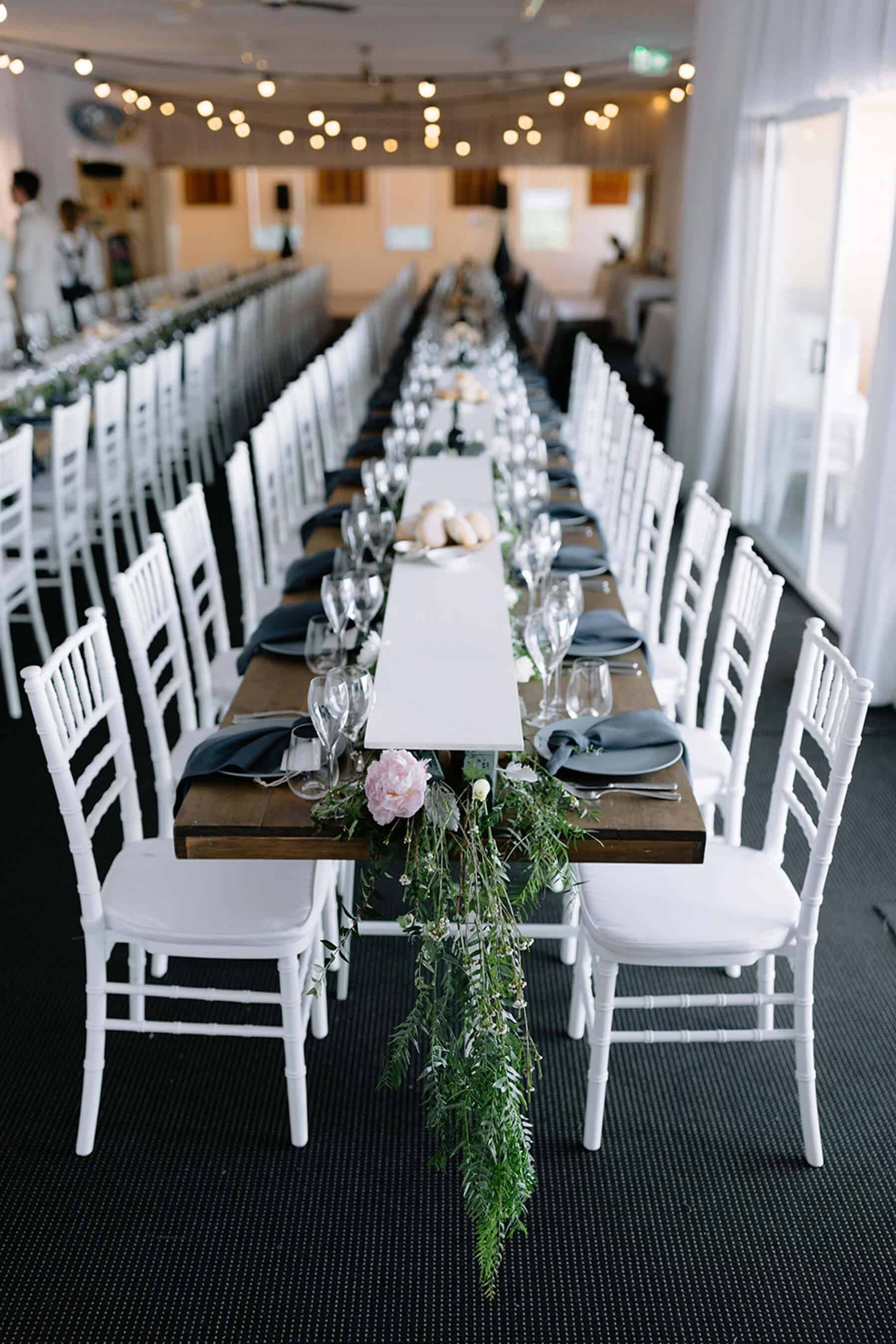 long wedding table with white chairs
