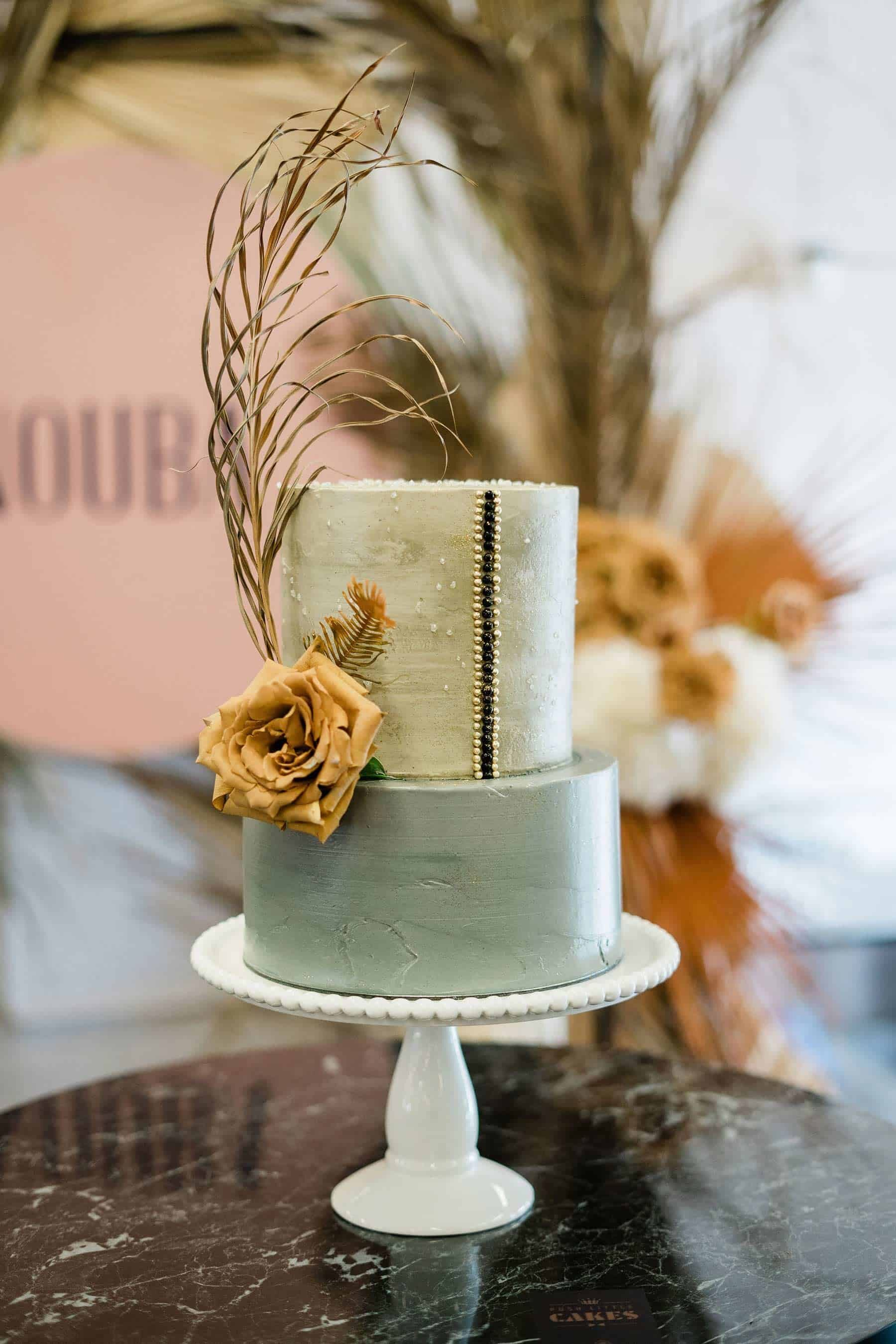 modern silver wedding cake with toffee rose and dried leaf topper