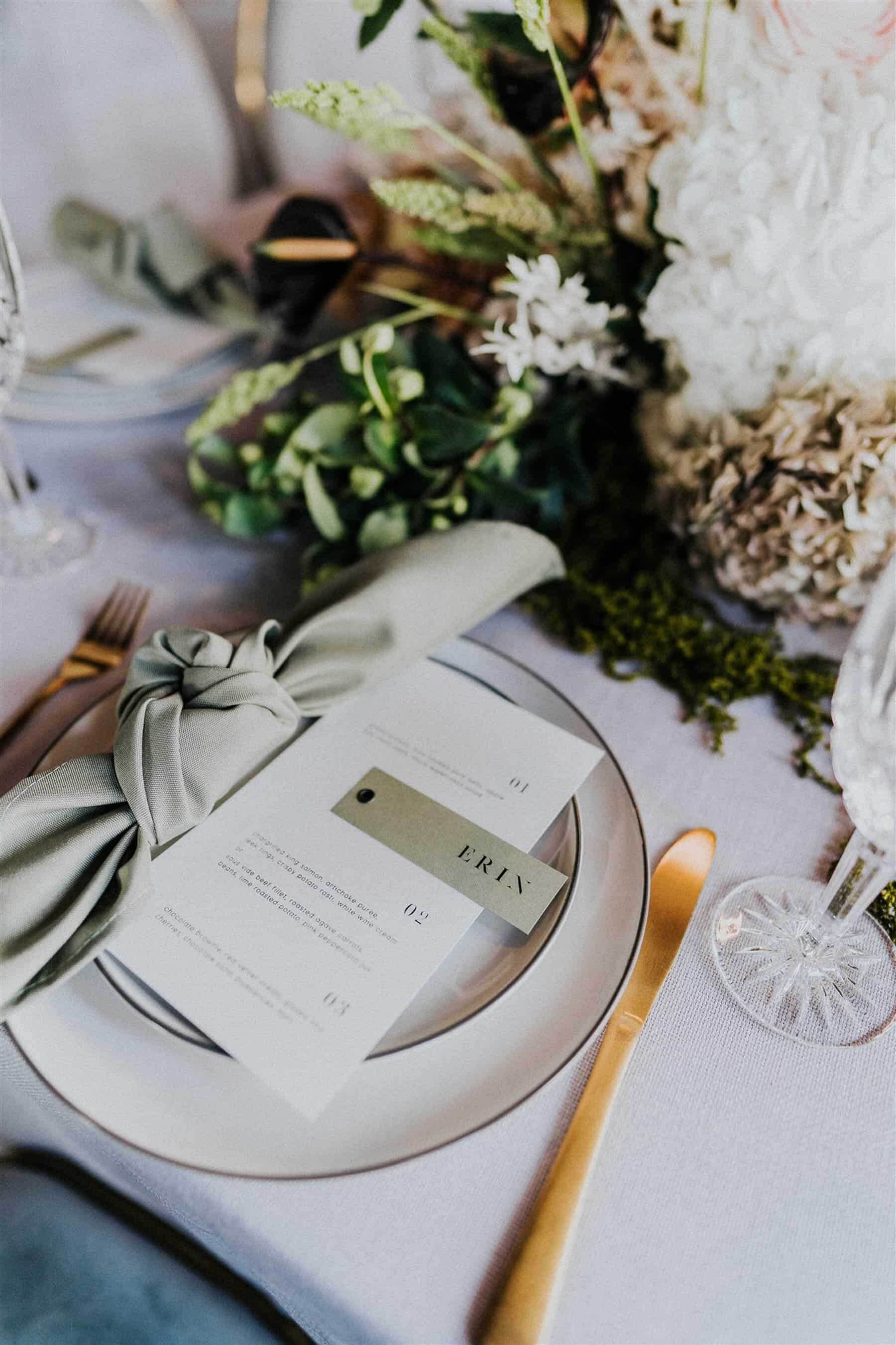 modern elegant place setting with green linen and gold cutlery
