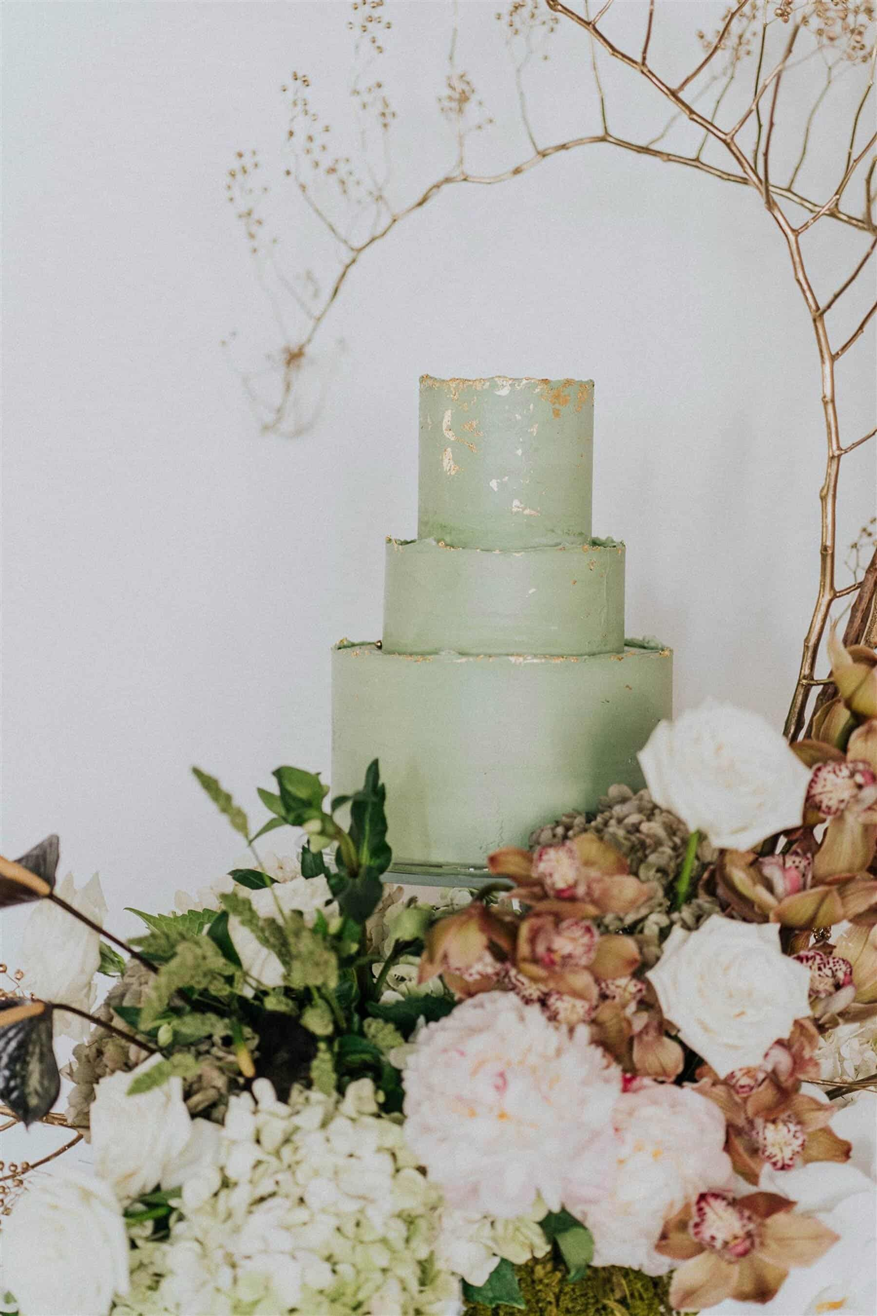 three tier green wedding cake with gold foil